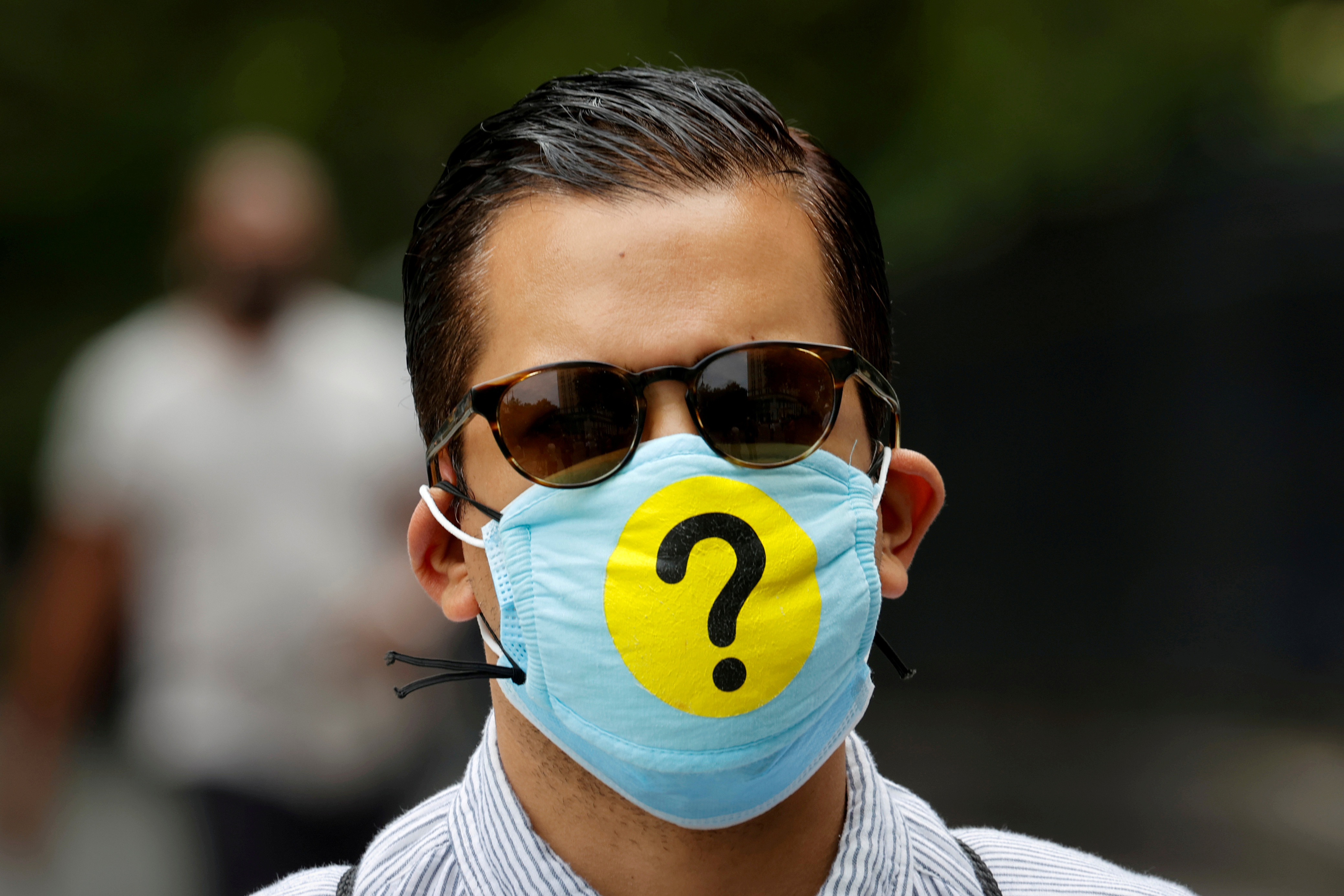 A man wears a protective face mask decorated with a question mark in lower Manhattan during the outbreak of the coronavirus disease (COVID-19) in New York, U.S., May 22, 2020. Picture taken May 22, 2020. REUTERS/Mike Segar     TPX IMAGES OF THE DAY - RC2FUG97KKF0