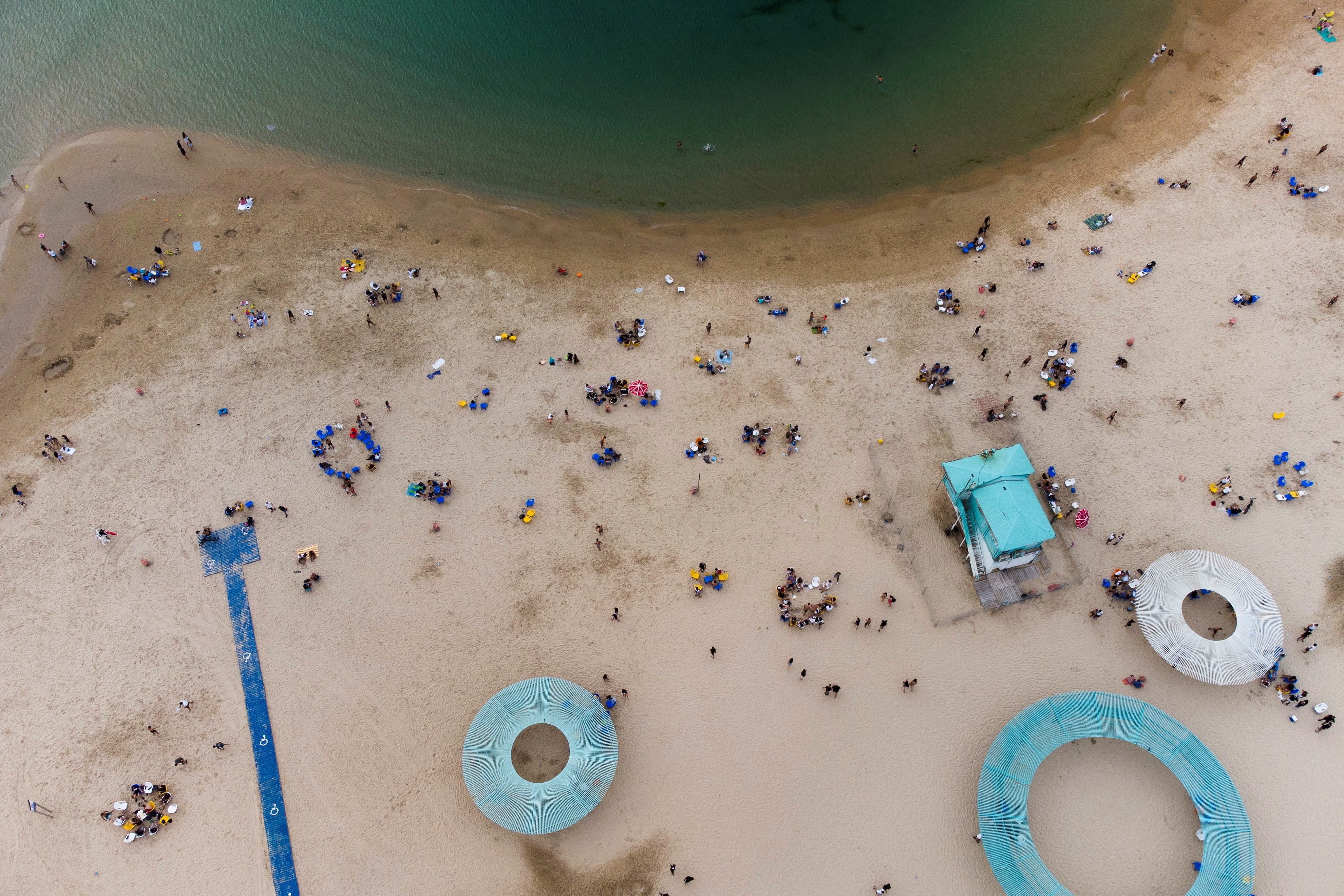 Israelis enjoy the beach of the Mediterranean during a heat wave as coronavirus disease (COVID-19) restrictions ease around the country, in Ashkelon Israel April 19, 2021. Picture taken with a drone. REUTERS/Amir Cohen - RC26ZM9KV543