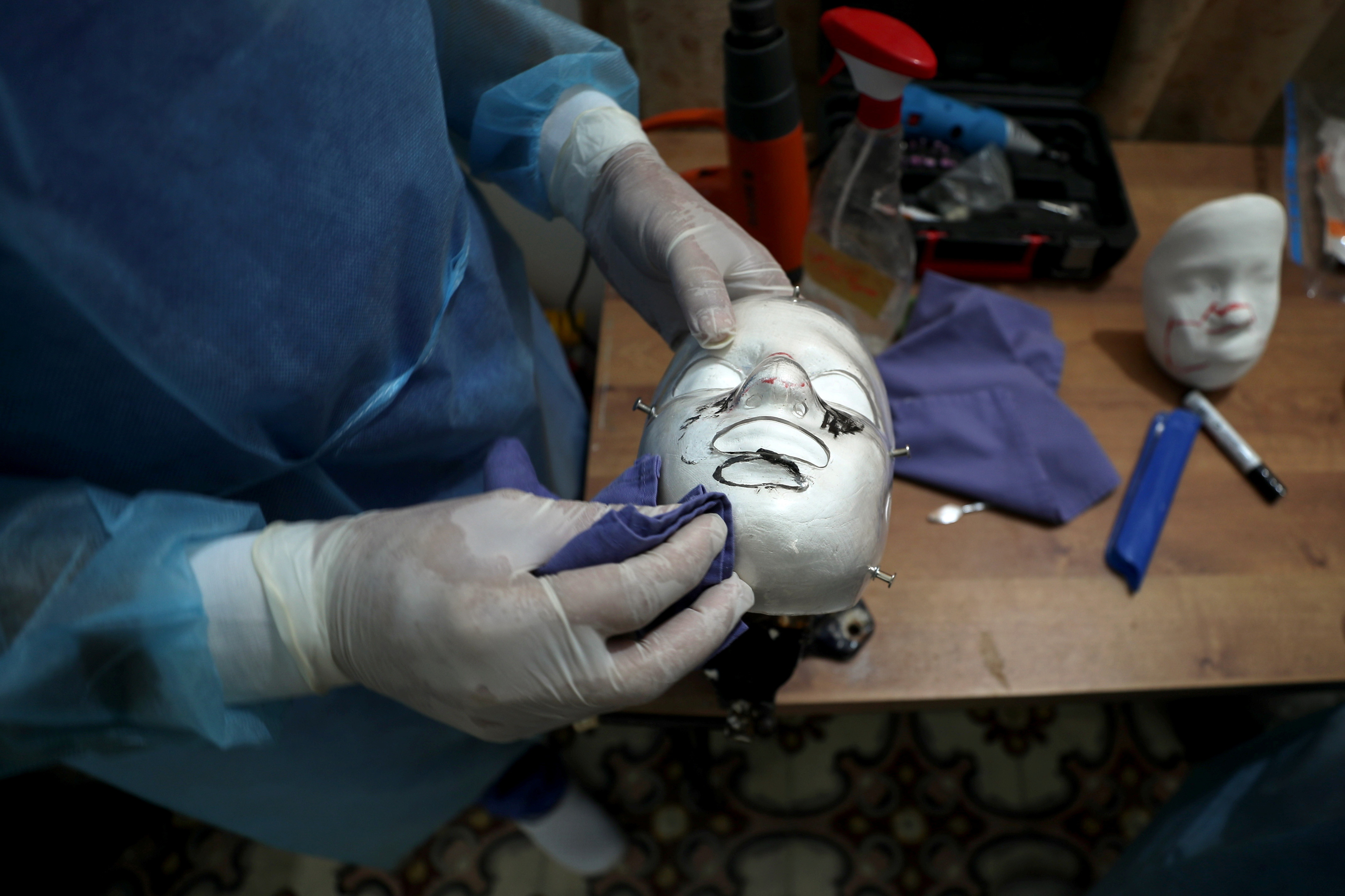 image of a physiotherapist putting a 3D transparent mask on the face of Palestinian boy Ahmed Al-Deeb, who is a burn victim of the Gaza bakery fire