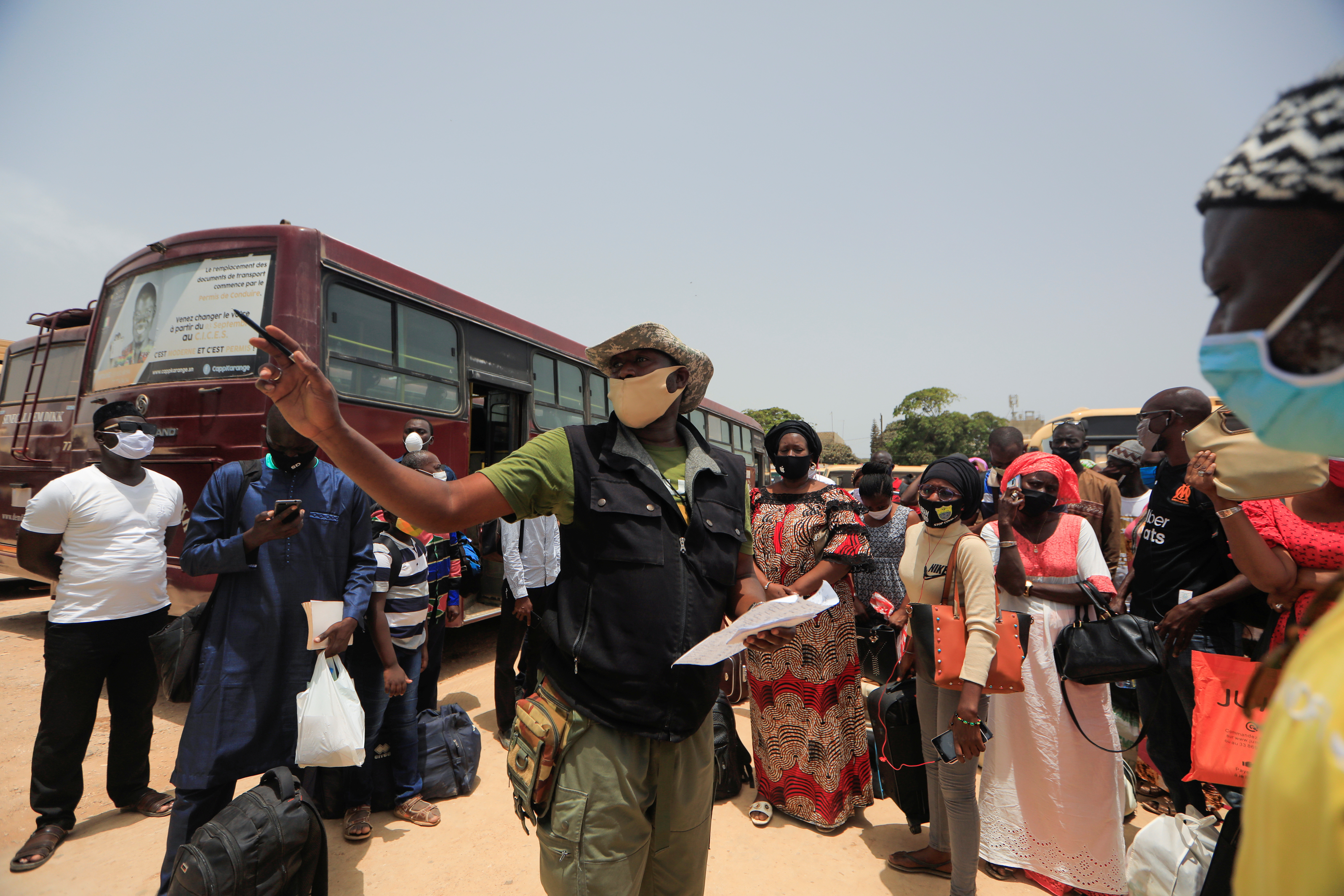 Senegalese teachers wait to board government-chartered buses taking them to rural schools.