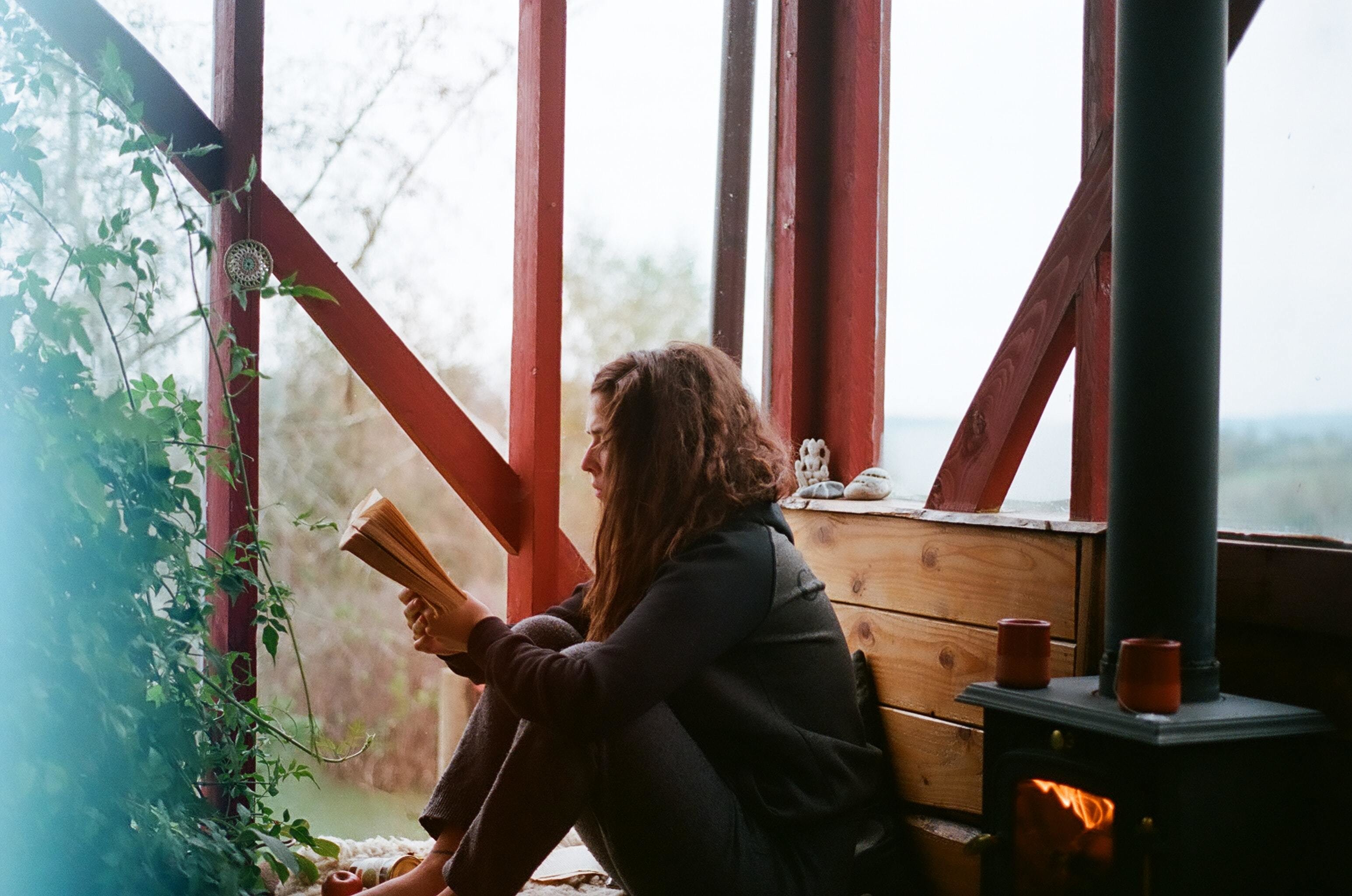 this woman is reading a printed book; printed books are still currently more popular than e-books.