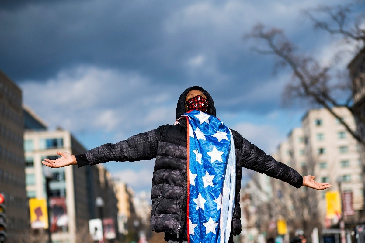 A supporter of U.S. President Joe Biden celebrates after he was sworn in as the 46th President of the United States, at Black Lives Matter Plaza, in Washington D.C., U.S. January 20, 2021. REUTERS/Eduardo Munoz - RC2UBL92OD1B