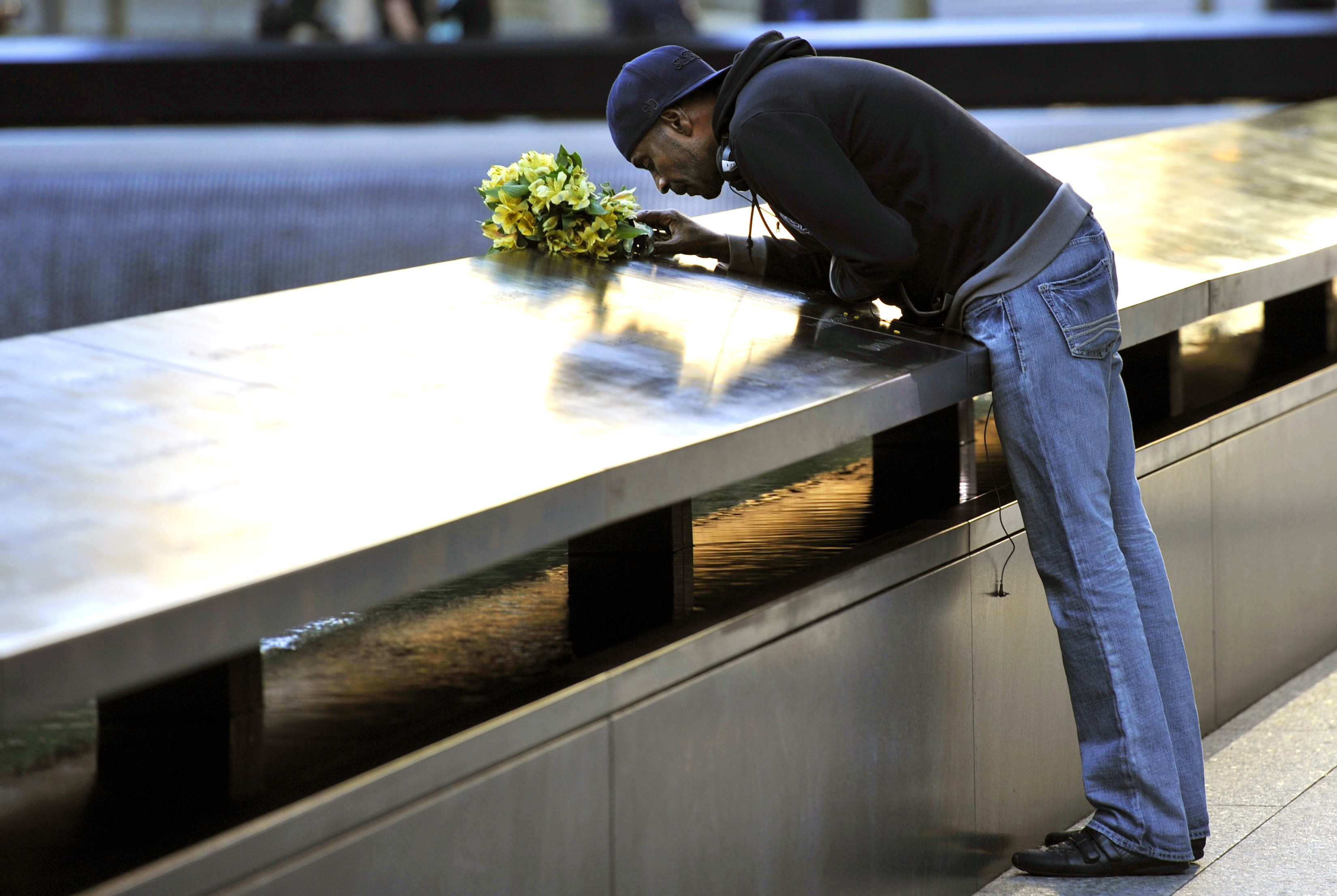 Dennis Swindell leans over to kiss the inscribed name of his partner, Gary Lee Bright, on the South Tower pool wall during ceremonies marking the 11th anniversary of the 9/11 attacks on the World Trade Center in New York