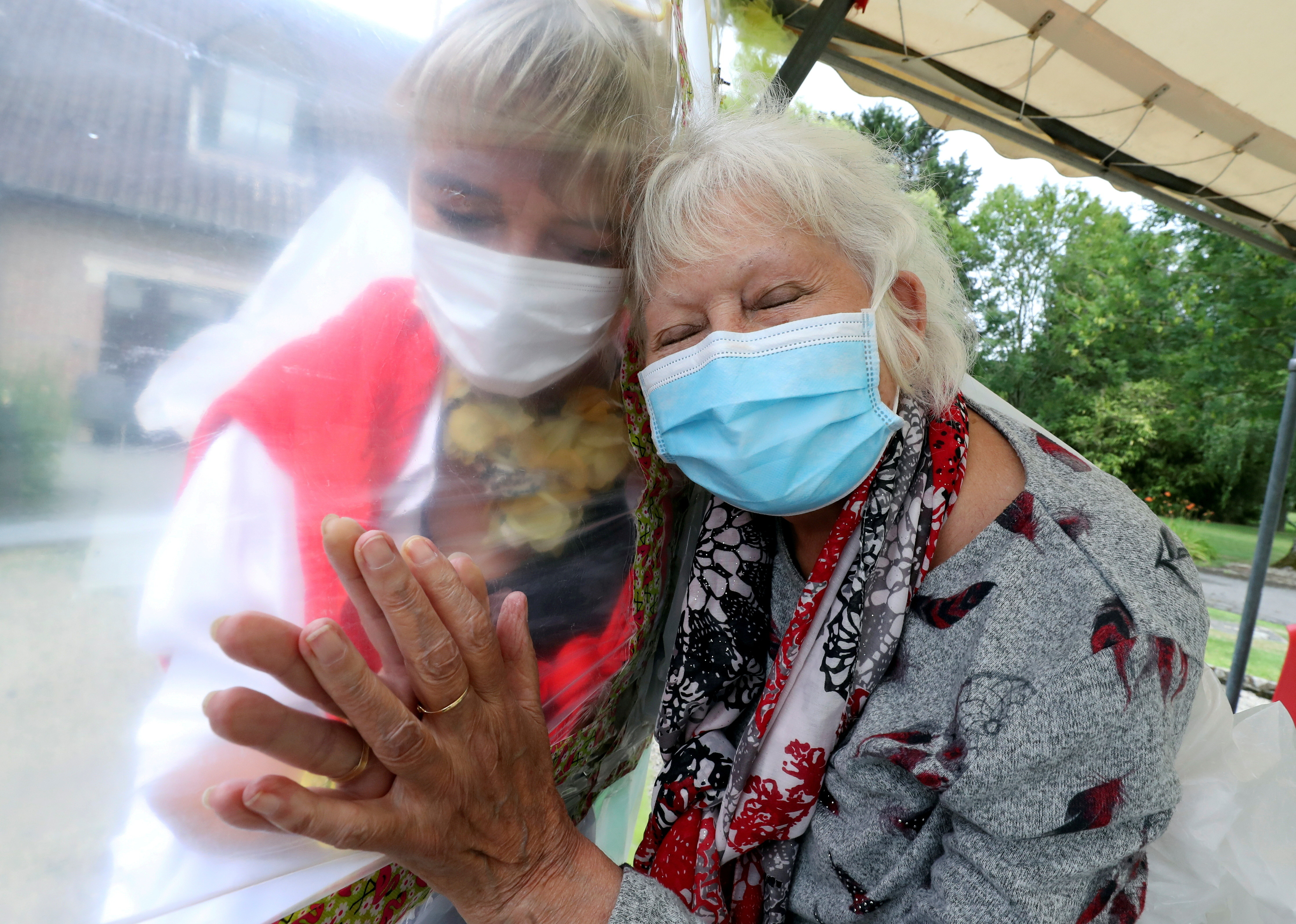 """Lily Hendrickx, 83, a resident at Belgian nursing home """"Le Jardin de Picardie"""" enjoys hugs and cuddles with Marie-Christine Desoer, the director of the residence, through a wall made with plastic sheets to protect against potential coronavirus disease (COVID-19) infection, in Peruwelz, Belgium, July 1, 2020. REUTERS/Yves Herman/File Photo     TPX IMAGES OF THE DAY     SEARCH """"GLOBAL COVID-19"""" FOR THIS STORY. SEARCH """"WIDER IMAGE"""" FOR ALL STORIES. - RC2NFK9YYM8J"""
