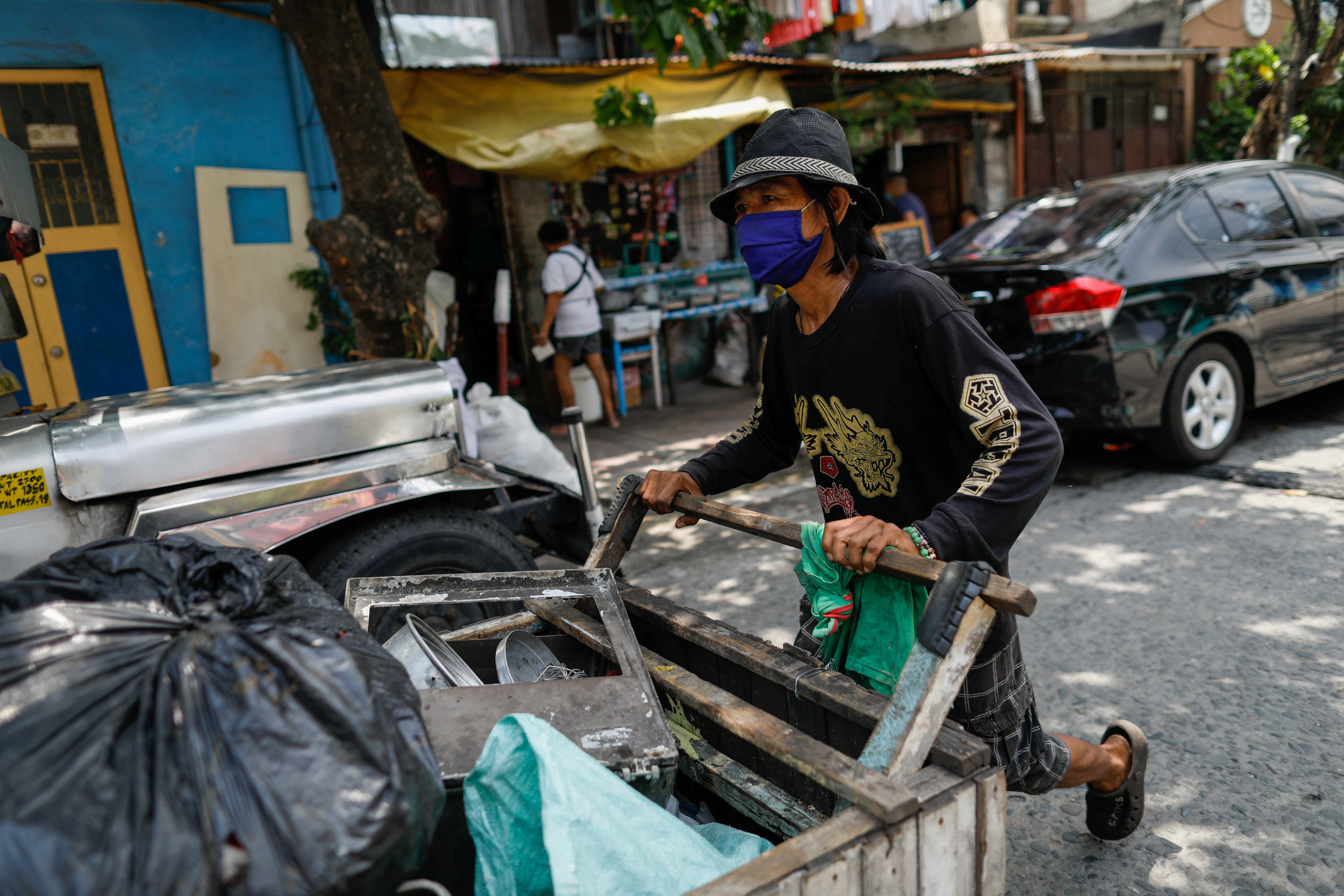 Waste picker Virgilio Estueta, 60, walks with his cart filled with trash amid the coronavirus disease (COVID-19) outbreak, in Quezon City, Metro Manila, Philippines, July 7, 2020. Picture taken July 7, 2020