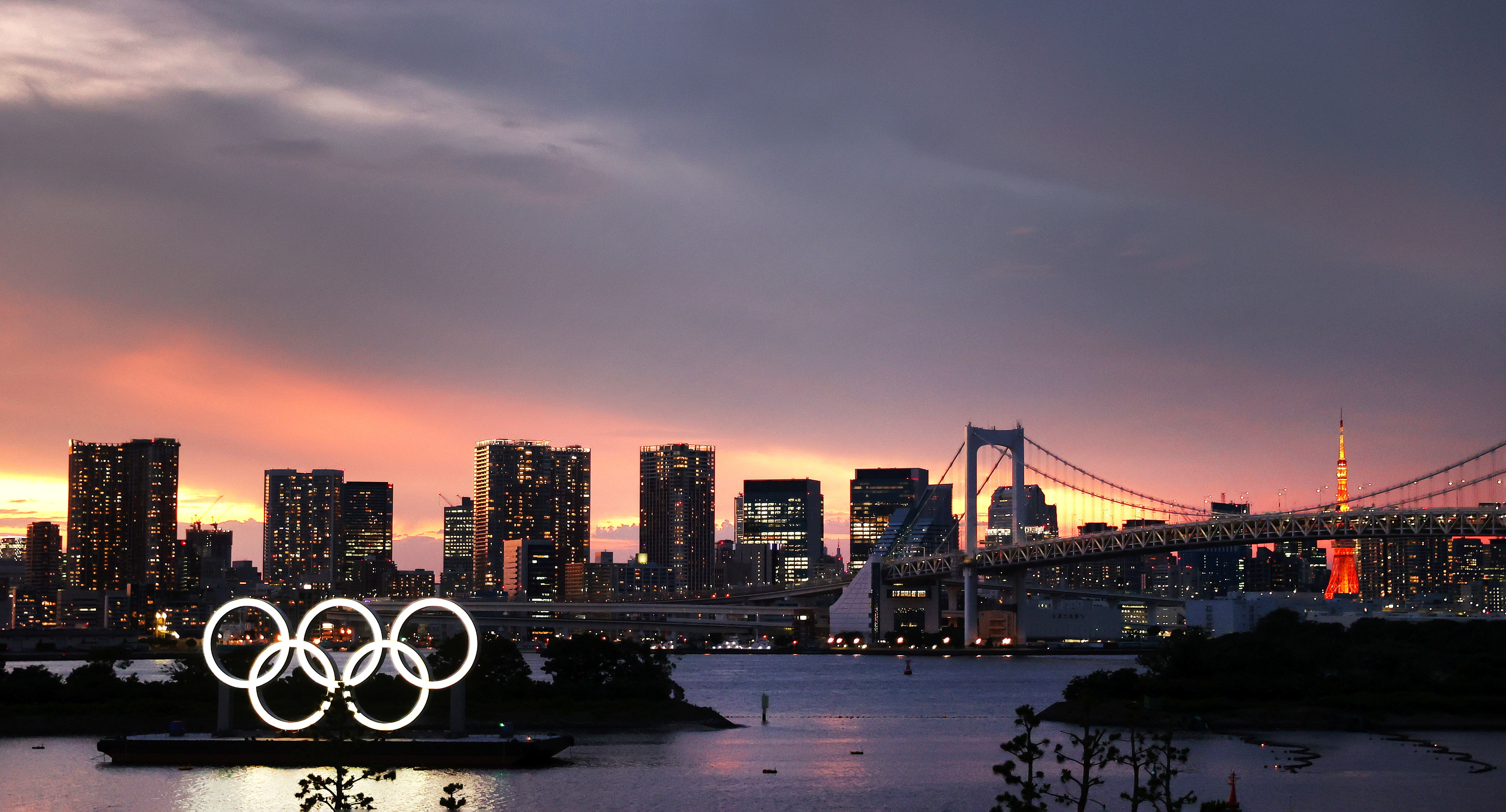 The Olympic Rings are seen in front of the skyline during sunset, three days ahead of the official opening of the Tokyo 2020 Olympic Games, in Tokyo, Japan, July 20, 2021.   REUTERS/Kai Pfaffenbach - RC2BOO9B9LCW