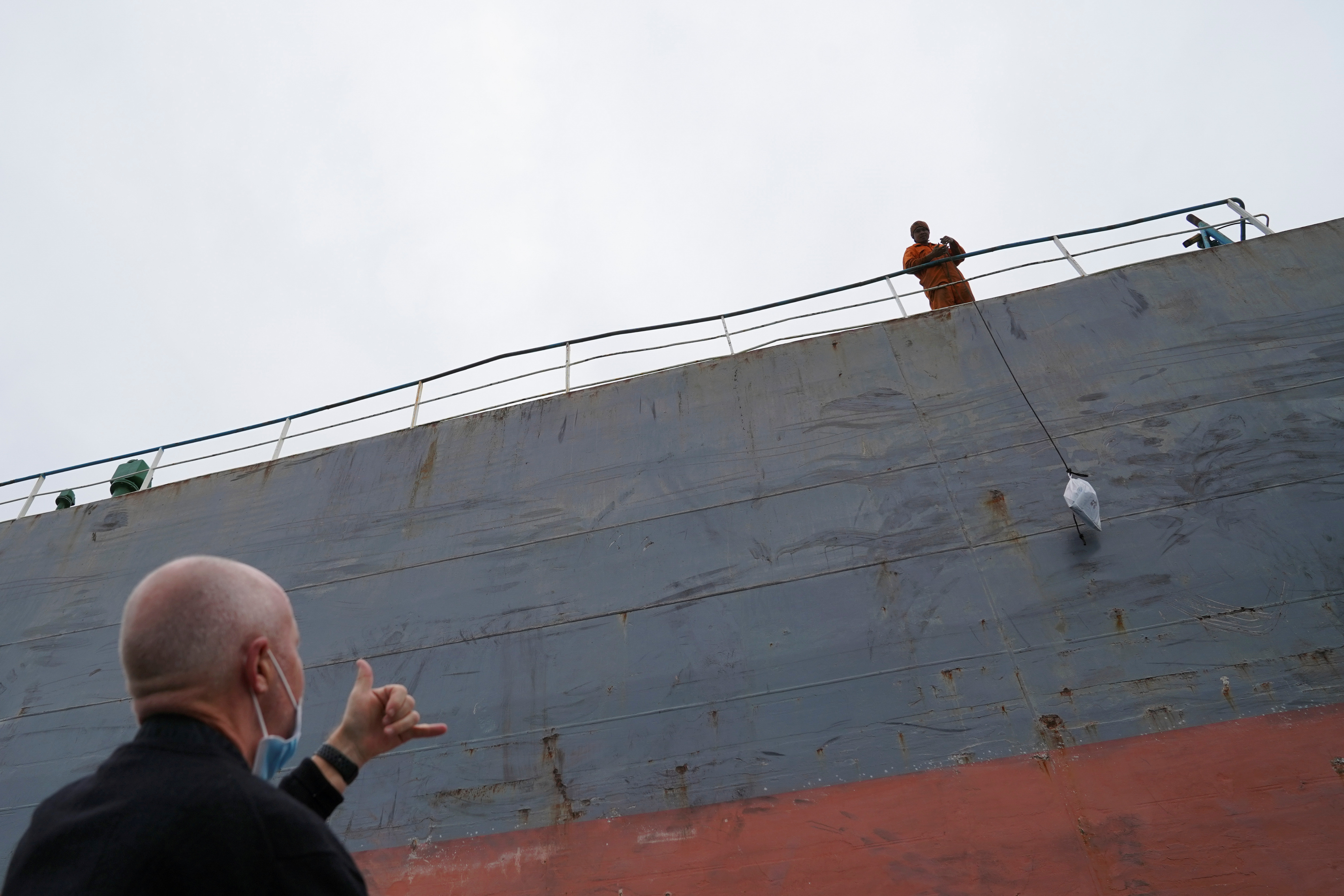 Reverend Stephen Miller of the Mission to Seafarers gestures at a sailor pulling up a bag on a bulk carrier, during a trip to deliver supplies to those stranded on visiting cargo vessels due to the coronavirus disease (COVID-19) pandemic, in Hong Kong, China March 22, 2021. Picture taken March 22, 2021. REUTERS/Lam Yik - RC2PKM91E4B6