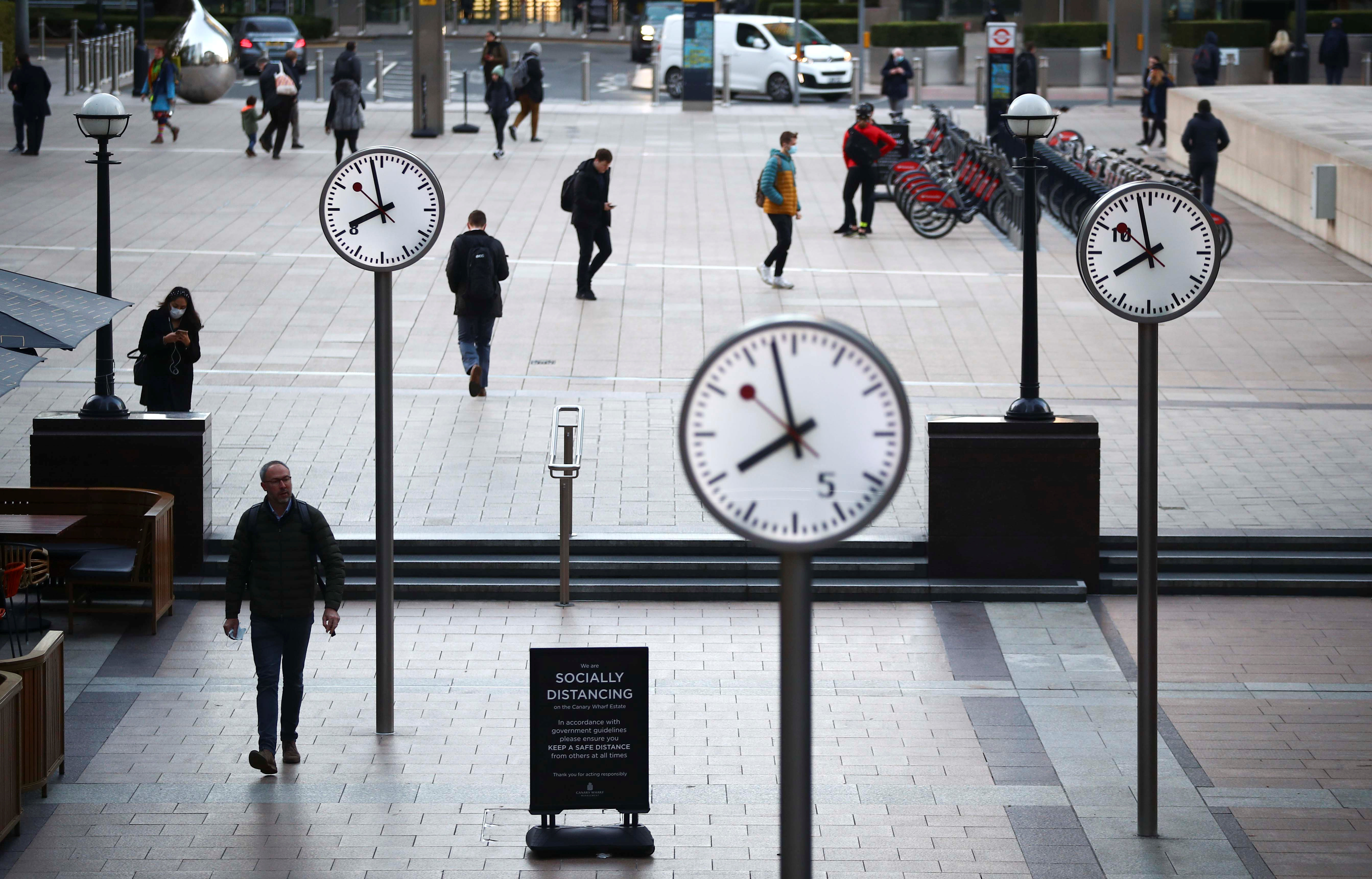 People walk during the morning rush hour in the Canary Wharf amid the outbreak of the coronavirus disease (COVID-19) in London Britain, October 15, 2020. REUTERS/Hannah McKay - RC2VIJ9GREF3