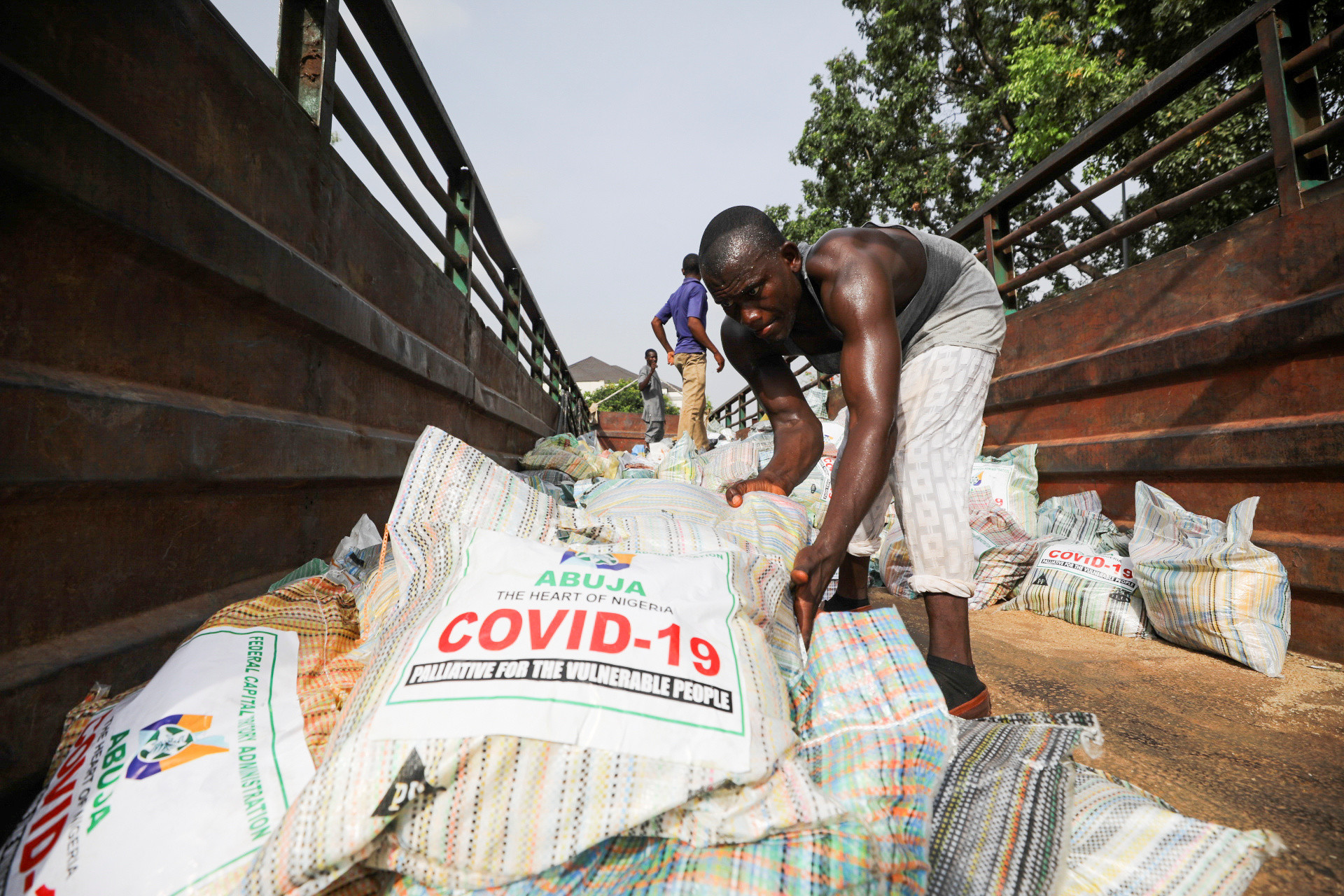 Men load sacks of rice among other food aid in a truck, to be distributed for those affected by procedures taken to curb the spread of coronavirus disease (COVID-19), in Abuja, Nigeria April 17, 2020. Picture taken April 17, 2020.