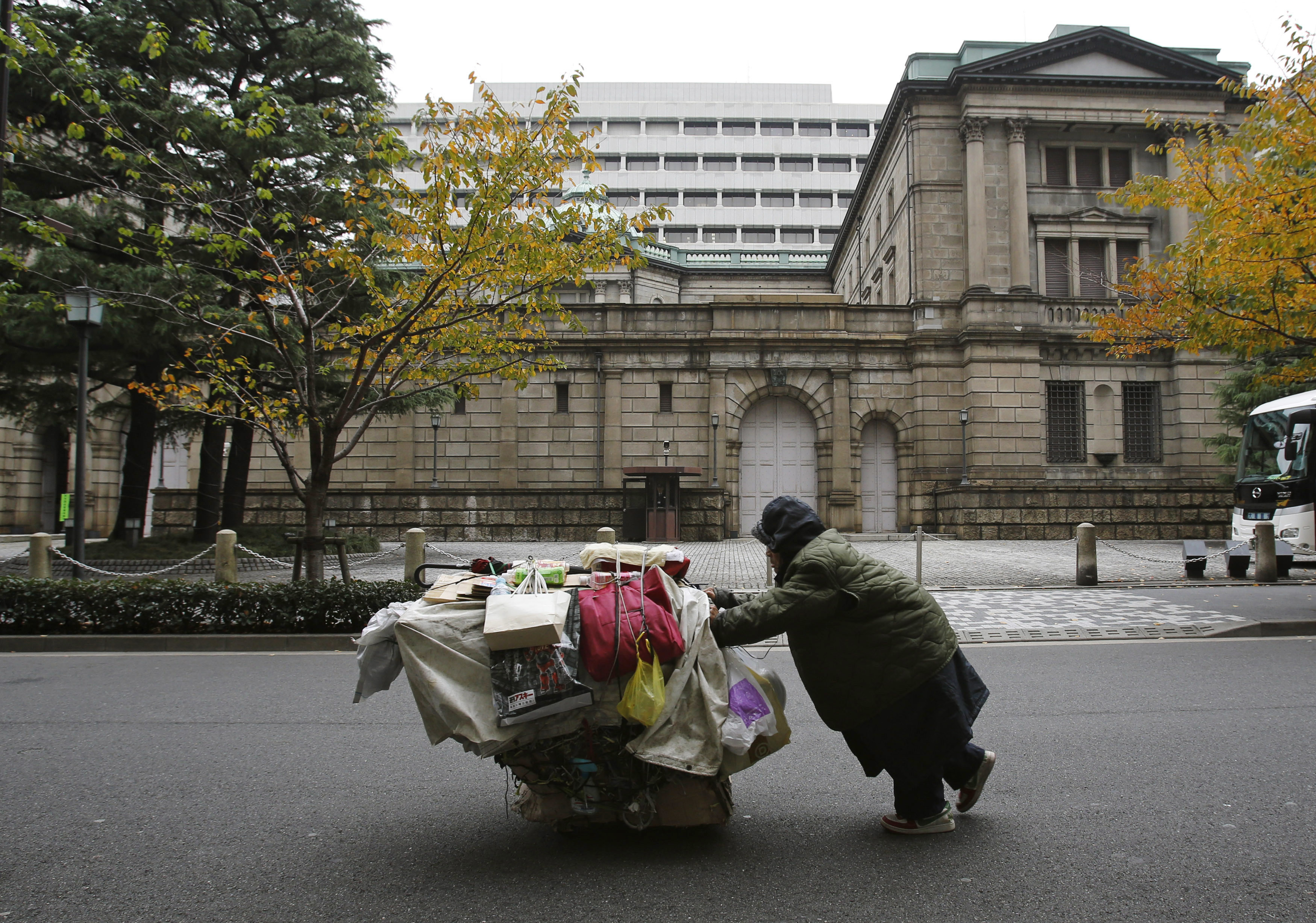 A man pushes a cart loaded with his belongings outside the Bank of Japan (BOJ) headquarters in Tokyo November 26, 2012.   REUTERS/Yuriko Nakao (JAPAN - Tags: SOCIETY BUSINESS POLITICS TPX IMAGES OF THE DAY) - GM1E8BQ0XTB01