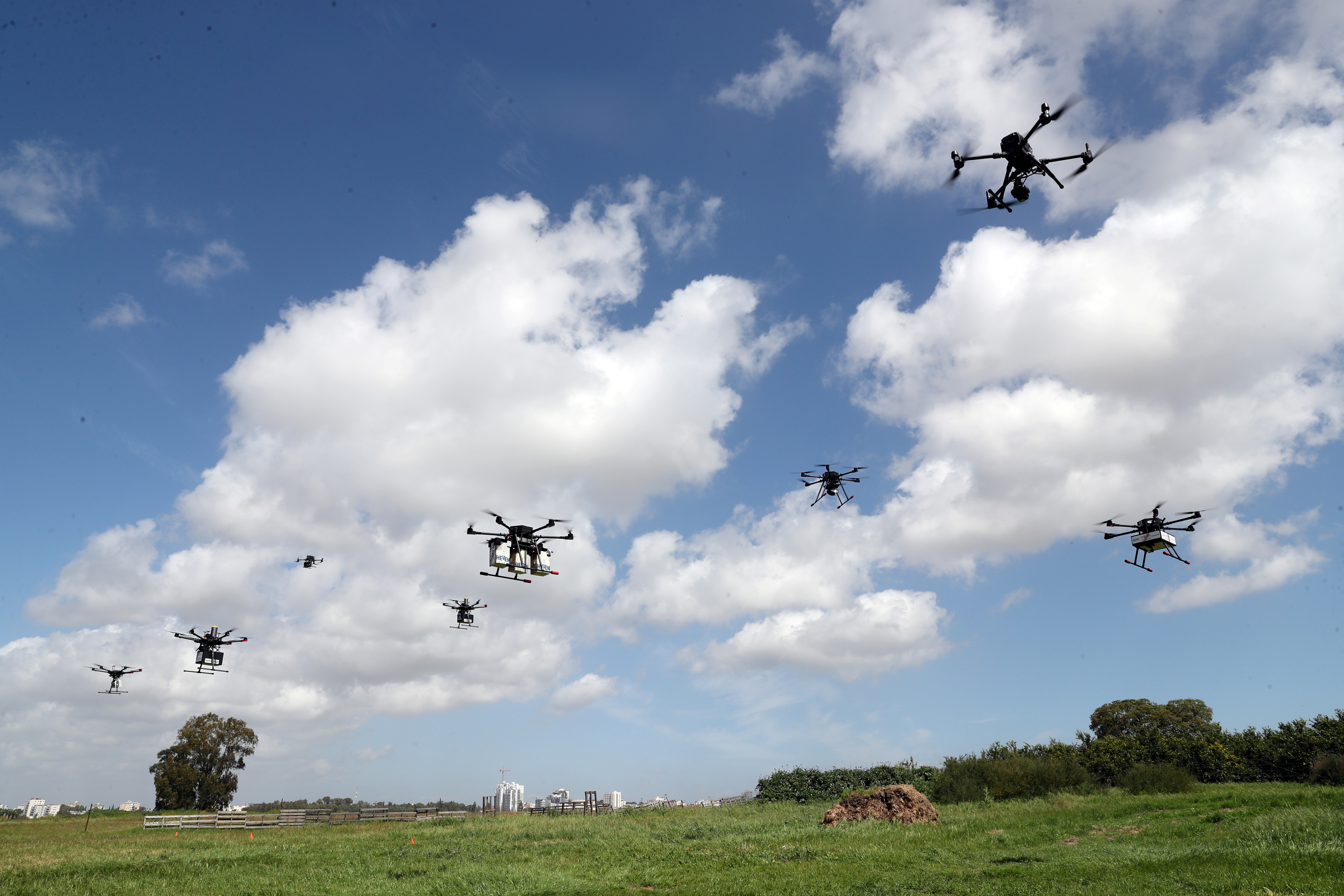 Delivery drones are seen midair during a demonstration whereby drones from various companies flew in a joint airspace and were managed by an autonomous control system in Haifa, in an open area near Hadera, Israel March 17, 2021. REUTERS/Ronen Zvulun - RC20DM9EY4TX