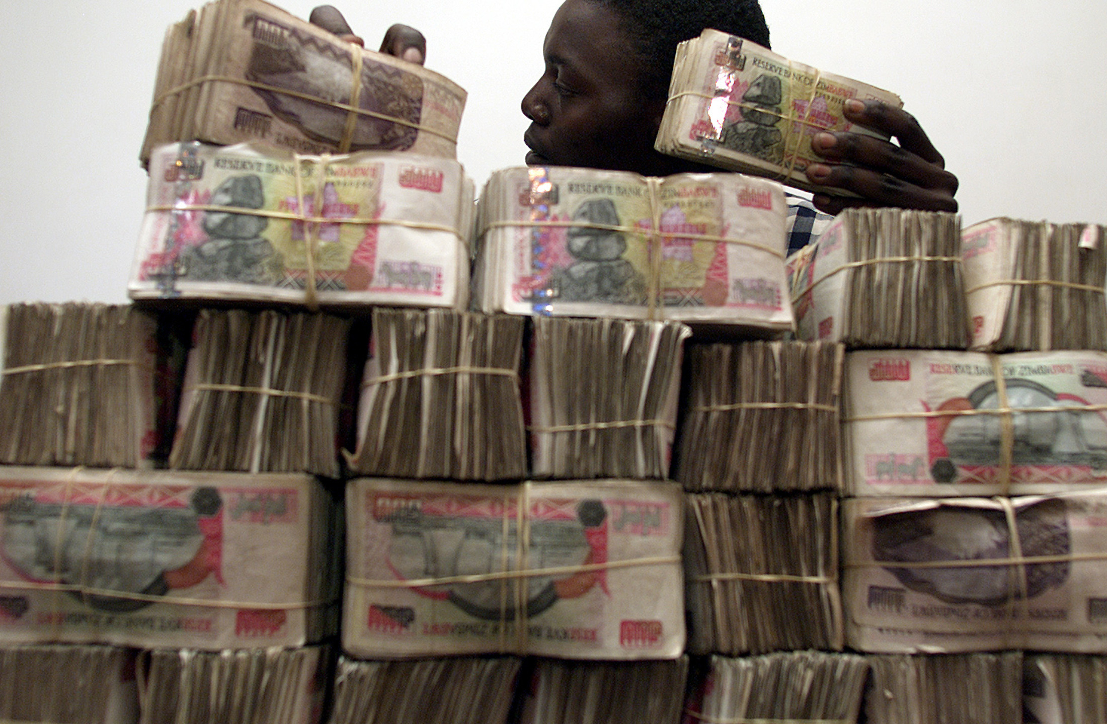 An unidentified Zimbabwean man piles up the black market equivalent ofUS$ 1000 (approximately 5 million Zimbabwe dollars) August 18, 2003.The government has outlawed the possession of cash in excess of 5million dollars from August 24, as it faces a critical shortage ofbanknotes due to hyper inflation in the crisis ridden country.(ZIMBABWE OUT) REUTERS/Howard BurdittHB/AA - RP4DRHYASMAC