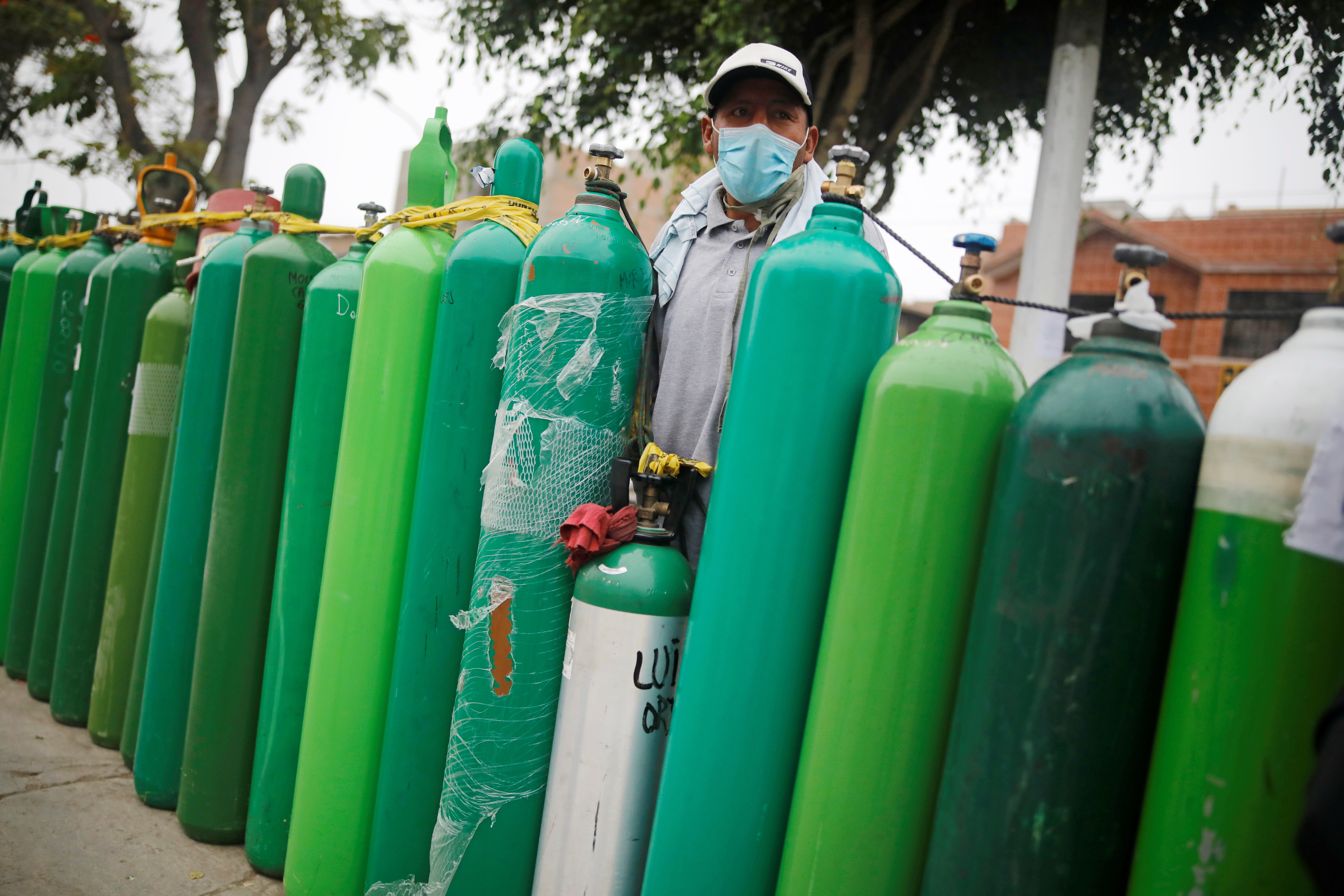 A man stands next to empty oxygen tanks to save a spot in the queue, as the supplier refills a tank per person and attends only up to 60 people a day, during the outbreak of the coronavirus disease (COVID-19), in Callao, Peru February 4, 2021. Picture taken February 4, 2021. REUTERS/Sebastian Castaneda - RC2OML9B317B