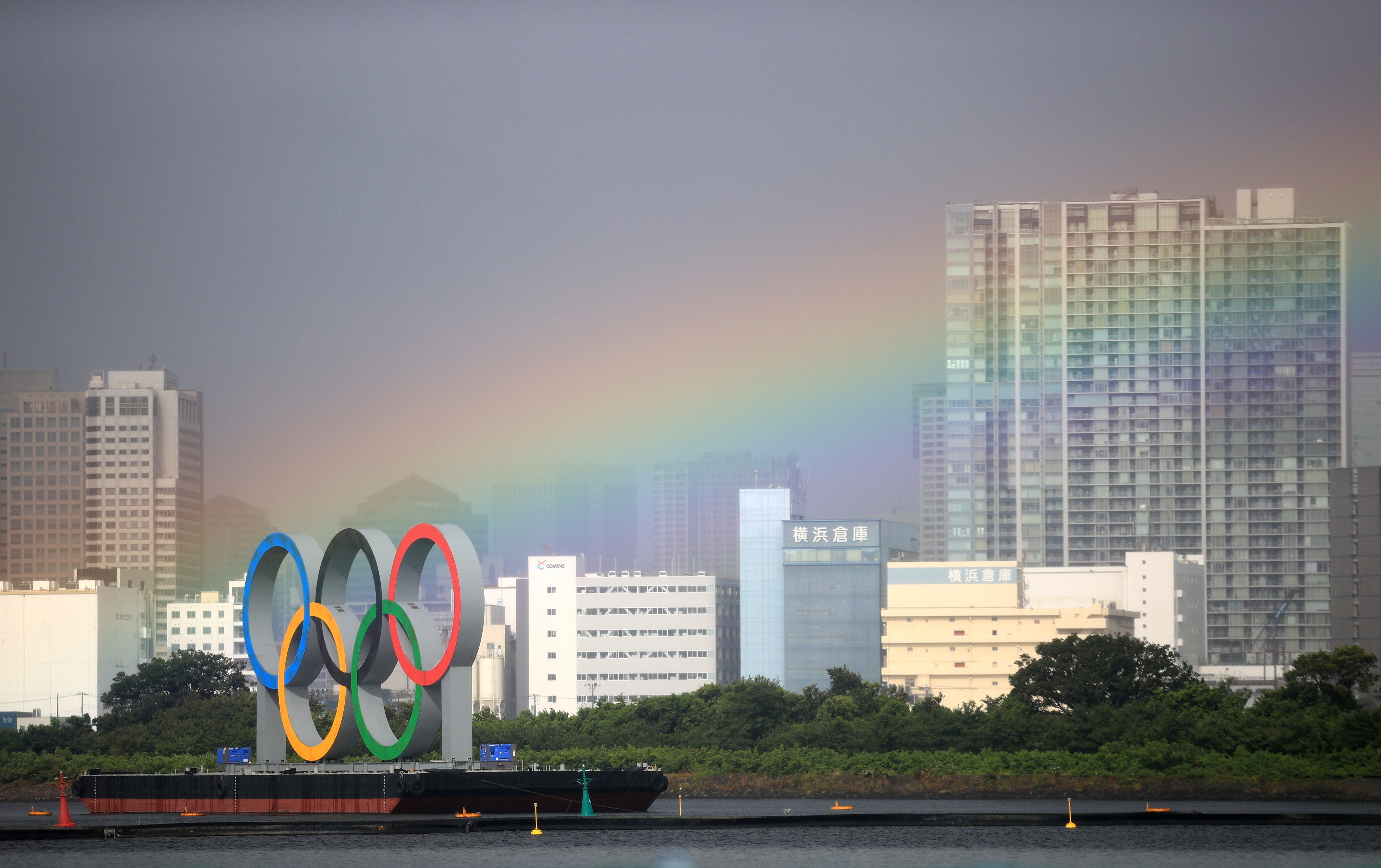 """Tokyo 2020 Olympics - Triathlon - Women's Olympic Distance - Final - Odaiba Marine Park, Tokyo, Japan July 27, 2021. A rainbow over city is seen during competition. REUTERS/Hannah Mckay/File Photo     SEARCH """"OLYMPICS DAY 5"""" FOR TOKYO 2020 OLYMPICS EDITOR'S CHOICE, SEARCH """"REUTERS OLYMPICS TOPIX"""" FOR ALL EDITOR'S CHOICE PICTURES - RC25TO97XK47"""