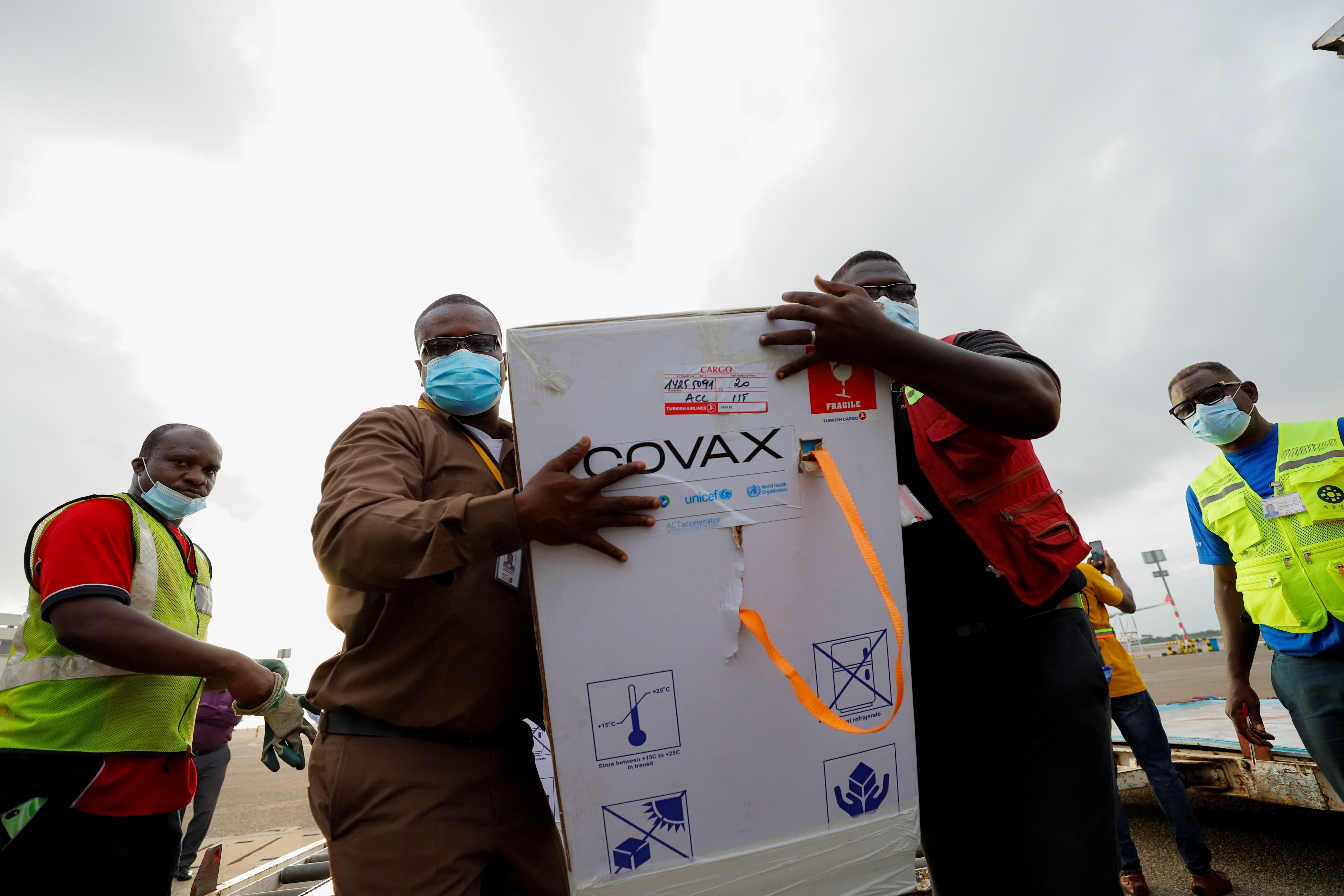 Workers carry boxes of Oxford/AstraZeneca coronavirus disease (COVID-19) vaccines supplied by the COVAX network
