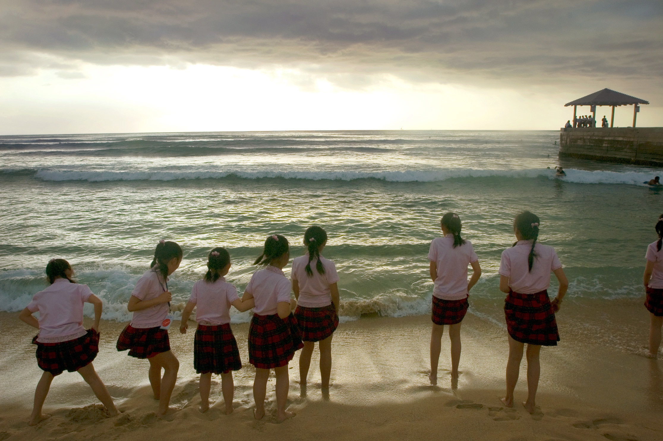 children play on a beach and look out to sea