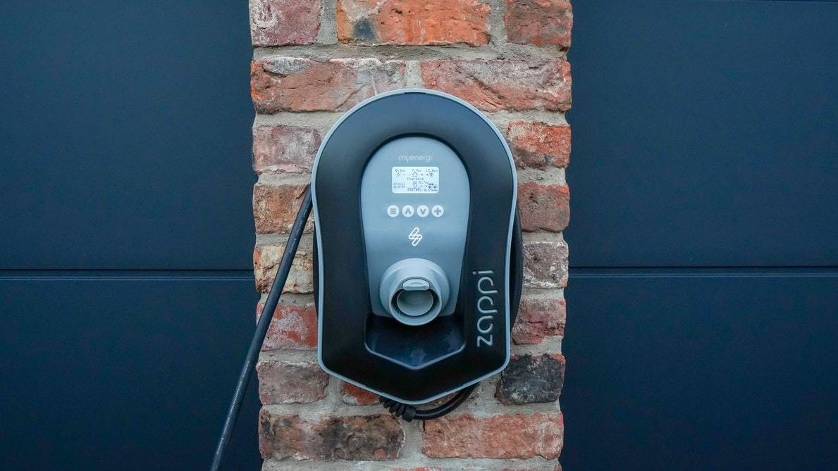 An EV charging station positioned on the side of a house.