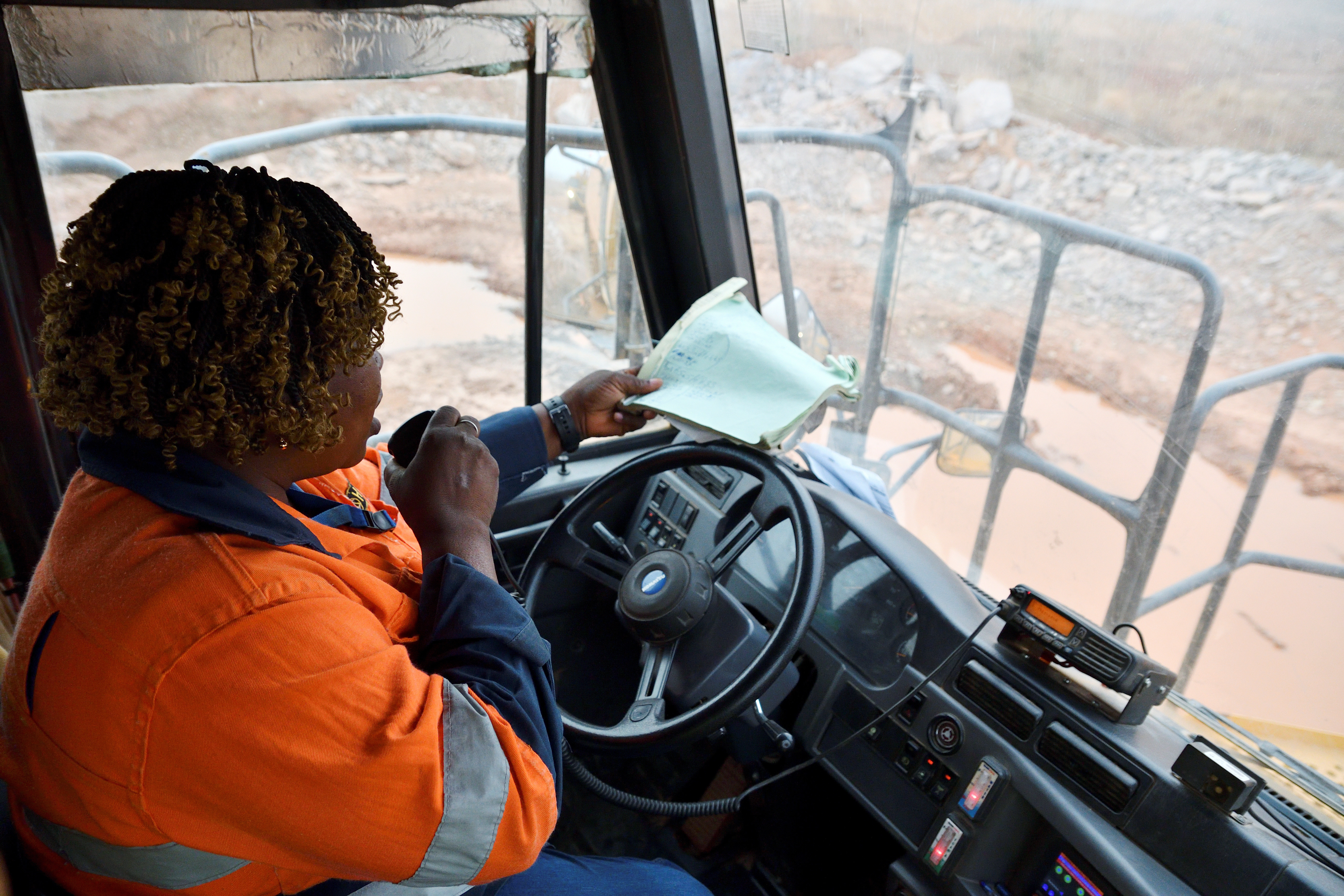 Tene Konate, 42, a truck driver, talks on a radio as she sits in her truck at the gold mine site, operated by Endeavour Mining Corporation in Hounde, Burkina Faso February 10, 2020. Picture taken February 10, 2020.