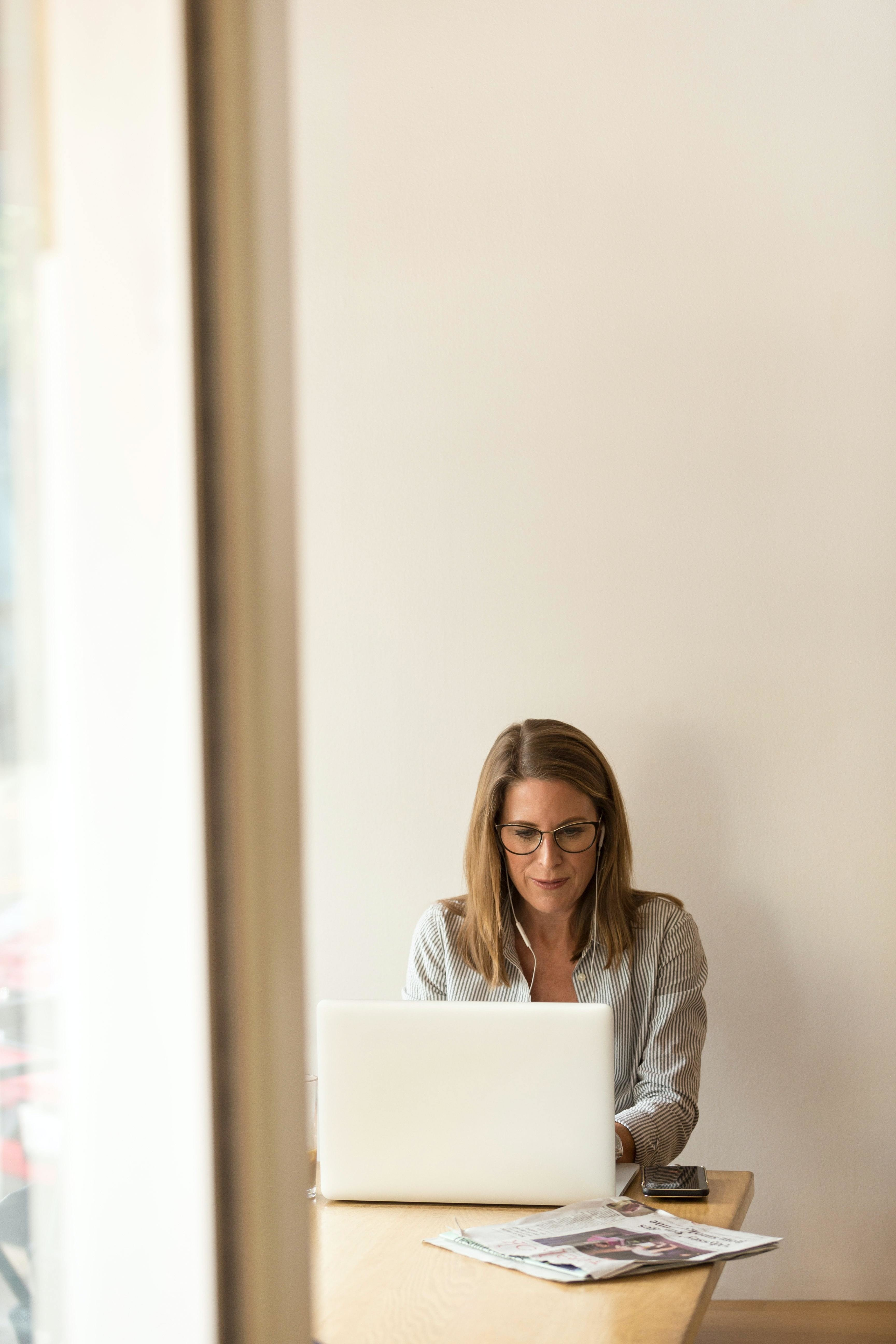 A women professionally dressed sits at a laptop.