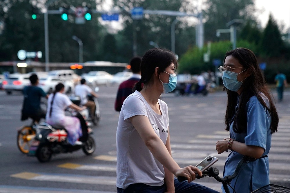 Women wearing face masks following the coronavirus disease (COVID-19) outbreak chat on a street in Beijing, China August 11, 2020. REUTERS/Tingshu Wang - RC2PBI92KGP7