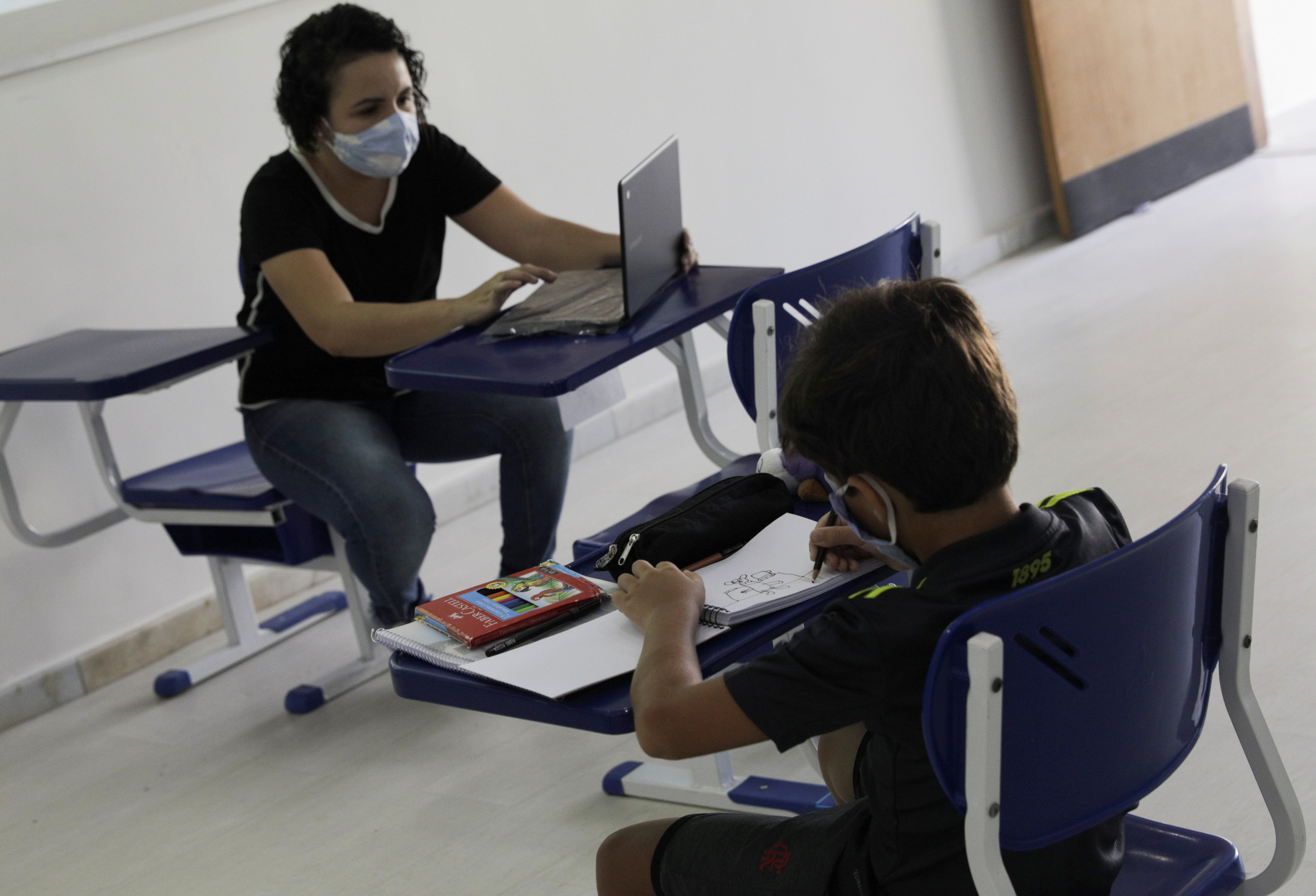 A student of Nova Escola school attends a class as his teacher talks to his colleagues studying on-line from their homes during the first day of the return of private schools in Rio de Janeiro, amid the outbreak of the coronavirus disease (COVID-19), Brazil, September 14, 2020. REUTERS/Ricardo Moraes - RC2JYI9Q2L6T