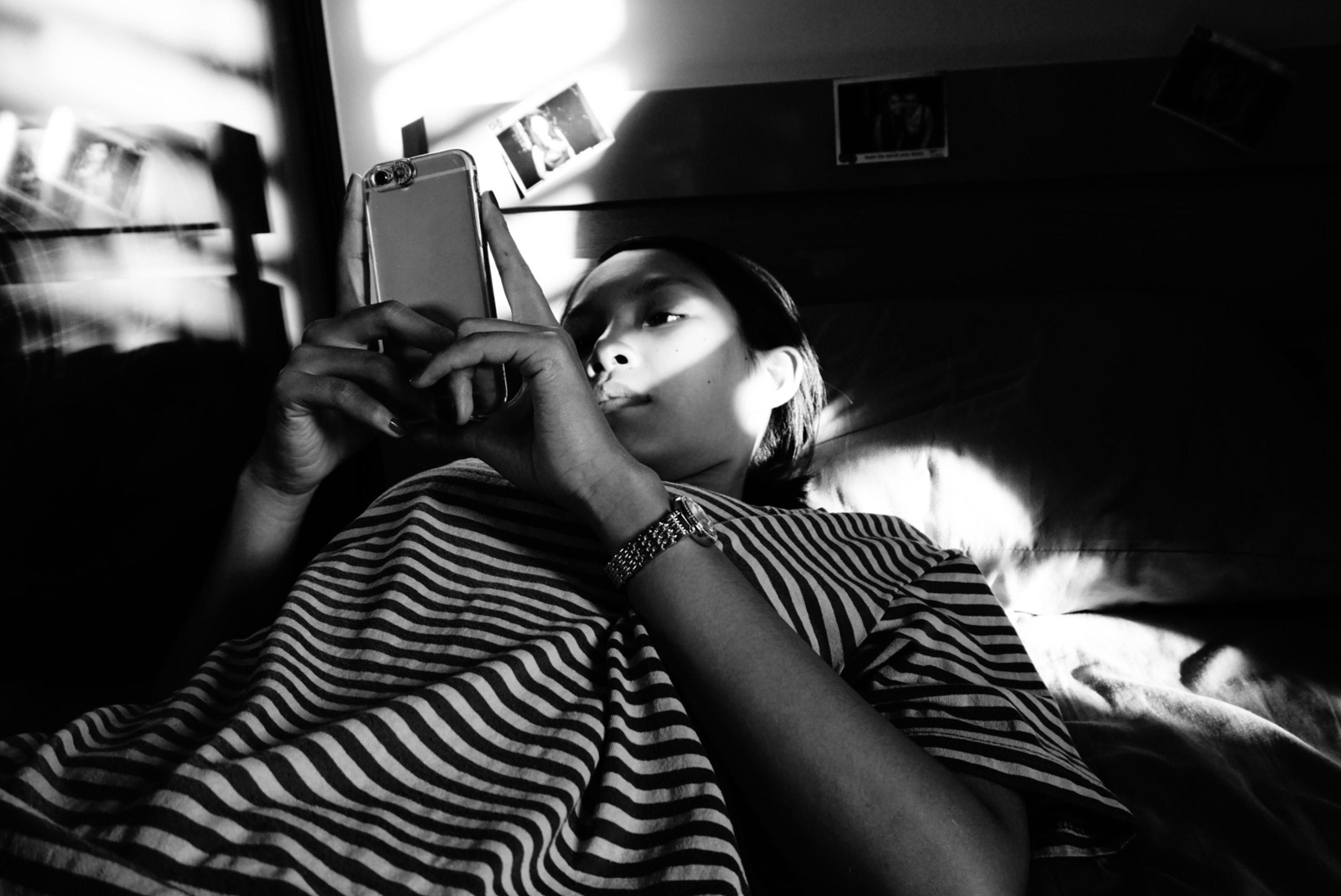 a woman lays on her bed whilst looking at a mobile phone in a black and white picture