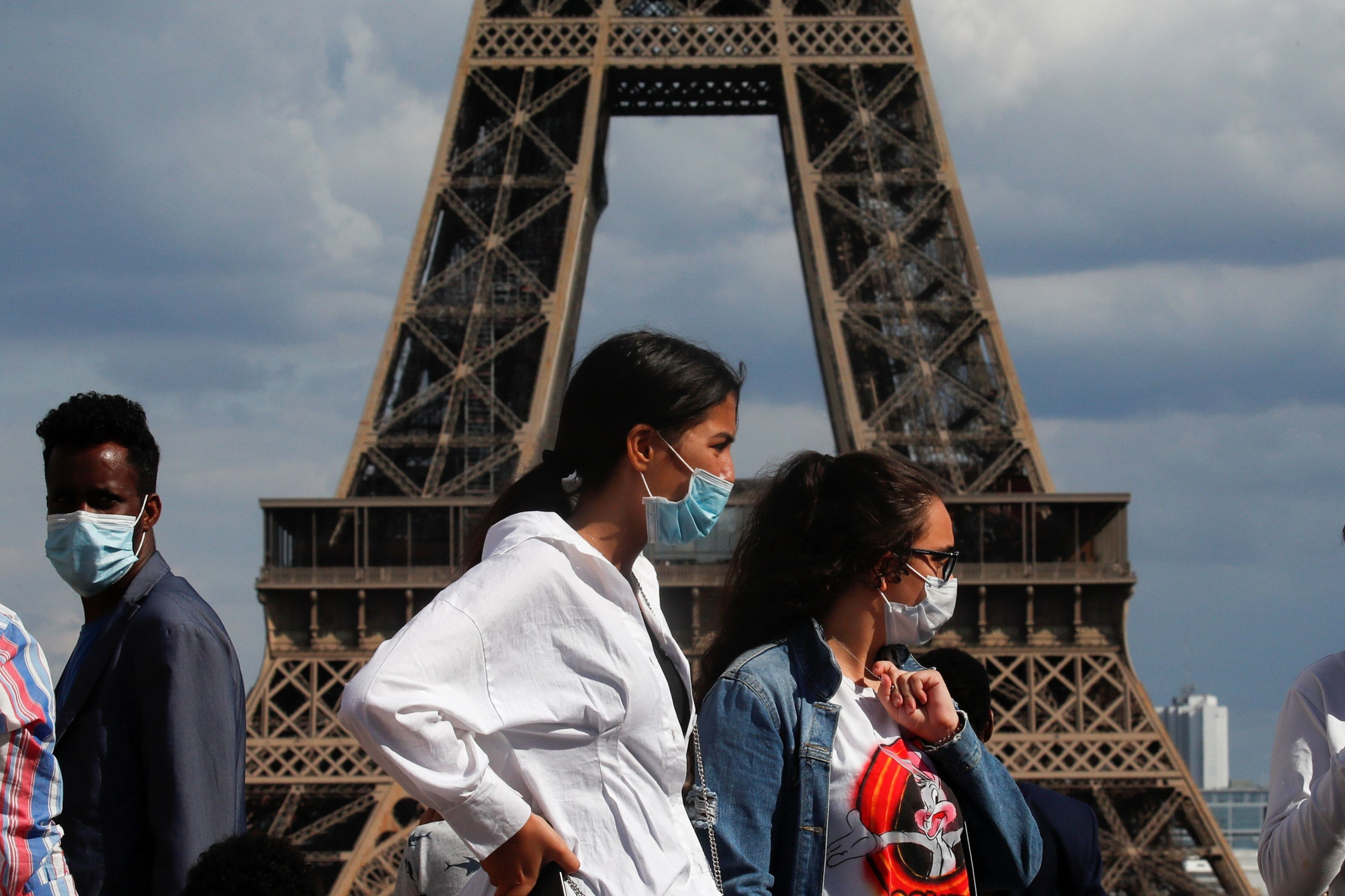 People wearing protective face masks walk at the Trocadero square near the Eiffel Tower in Paris as France reinforces mask-wearing as part of efforts to curb a resurgence of the coronavirus disease (COVID-19) across the country, August 3, 2020. REUTERS/Gonzalo Fuentes - RC2H6I9W6X3Y