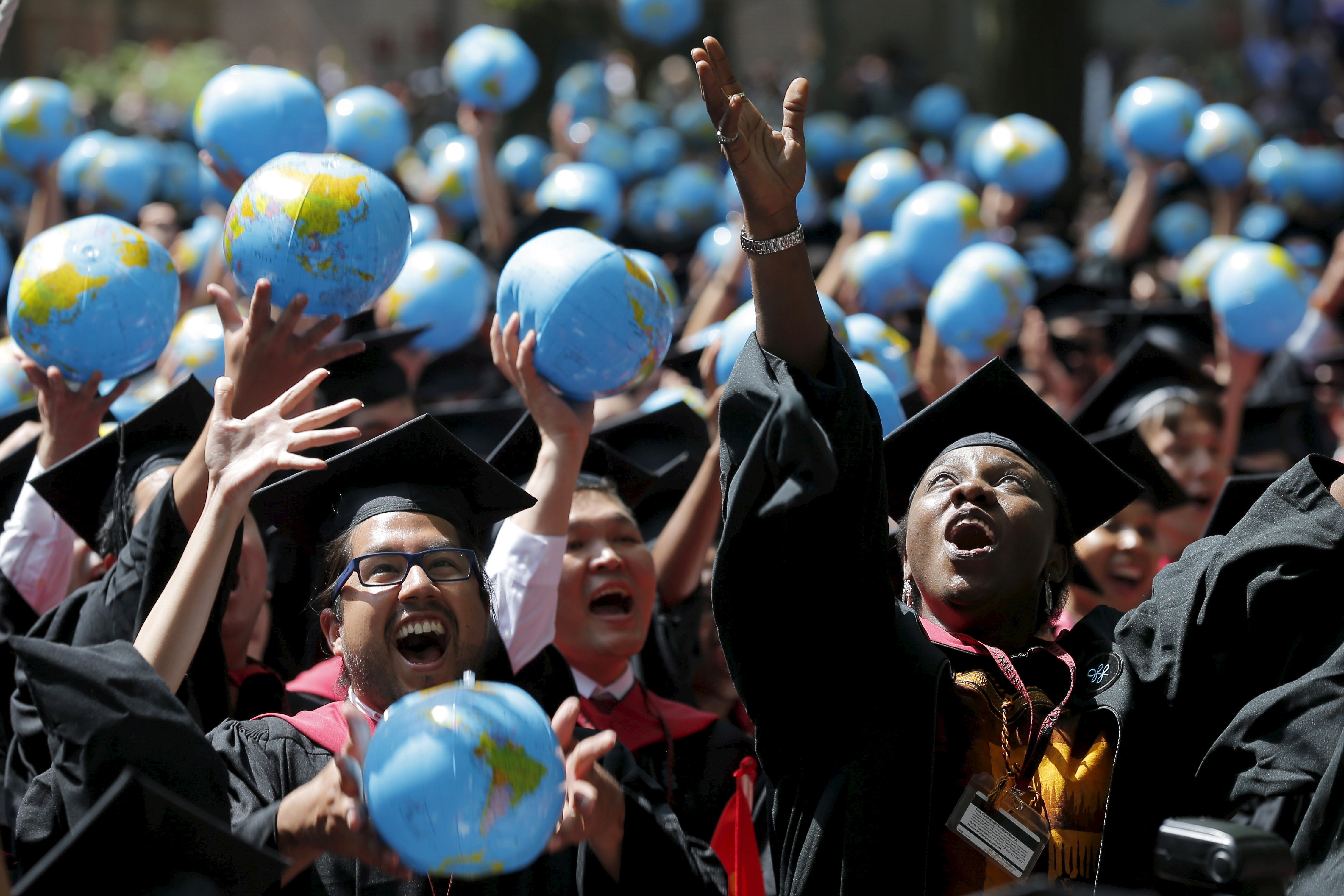Olufunke Michaels (R) and her classmates celebrate after receiving their degrees from the John F. Kennedy School of Government during the 364th Commencement Exercises at Harvard University in Cambridge, Massachusetts May 28, 2015.    REUTERS/Brian Snyder      TPX IMAGES OF THE DAY      - GF10000110401