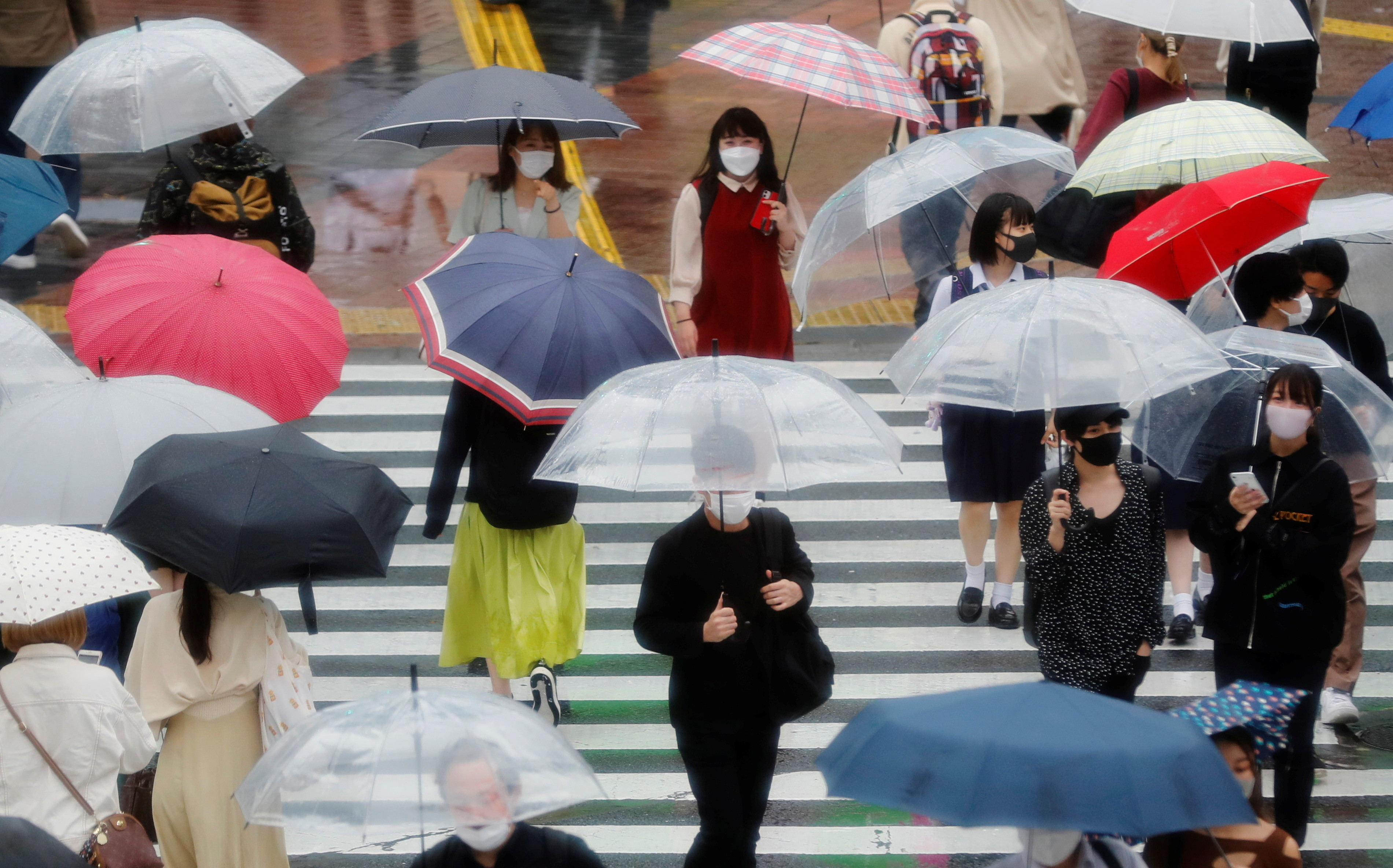 Pedestrians wearing protective masks, following the coronavirus disease (COVID-19) outbreak, makes their way in the rain ahead of the Tokyo 2020 Olympic Games in Tokyo, Japan, May 27, 2021.   REUTERS/Kim Kyung-Hoon - RC27ON9NH1BQ