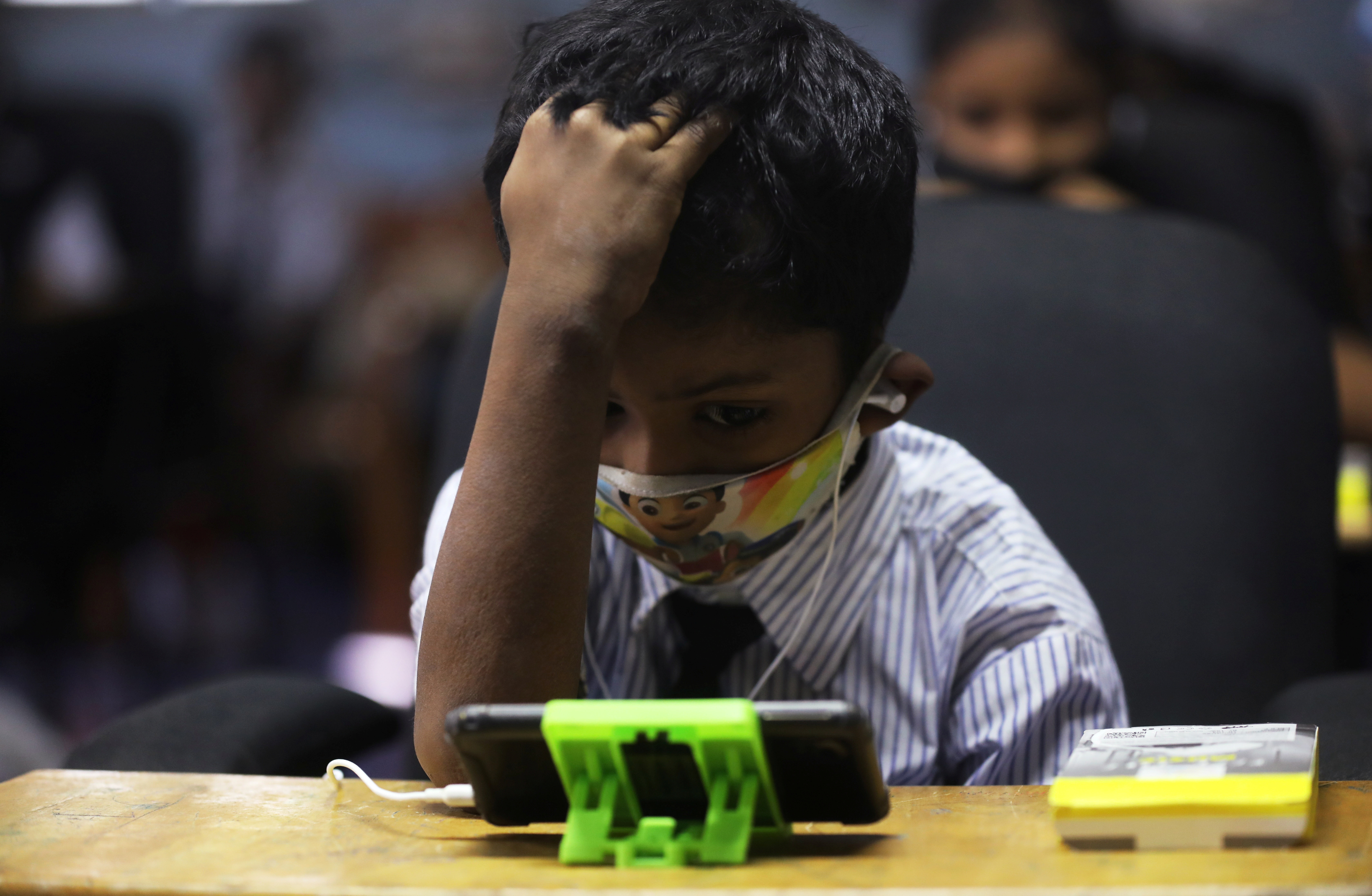 A student watches an online lecture on a mobile phone, inside a digital mobile education library, initiated to provide mobile phones to chidren who have no access to them for their education classes amidst the spread of the coronavirus disease (COVID-19) in Mumbai, India, October 16, 2020. REUTERS/Francis Mascarenhas - RC2KJJ932W9L