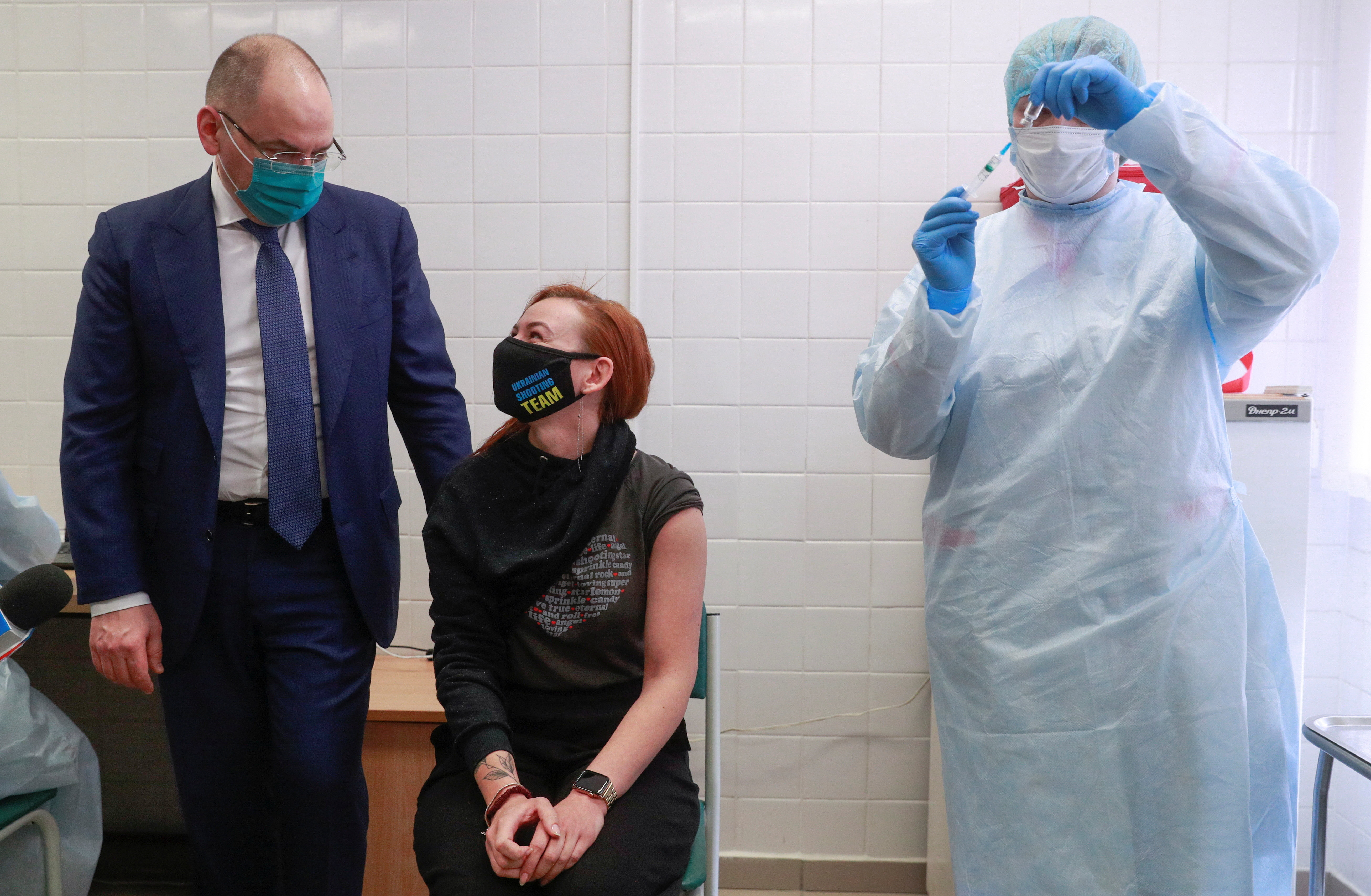 Ukrainian Health Minister Maksym Stepanov speaks with Anna Ilina, a member of the Ukrainian Olympic shooting team that will compete in the Tokyo 2020 Olympics, as she waits before receiving a dose of Chinese-developed CoronaVac vaccine against the coronavirus disease (COVID-19) in Kyiv, Ukraine April 15, 2021. REUTERS/Valentyn Ogirenko - RC29WM9FP122