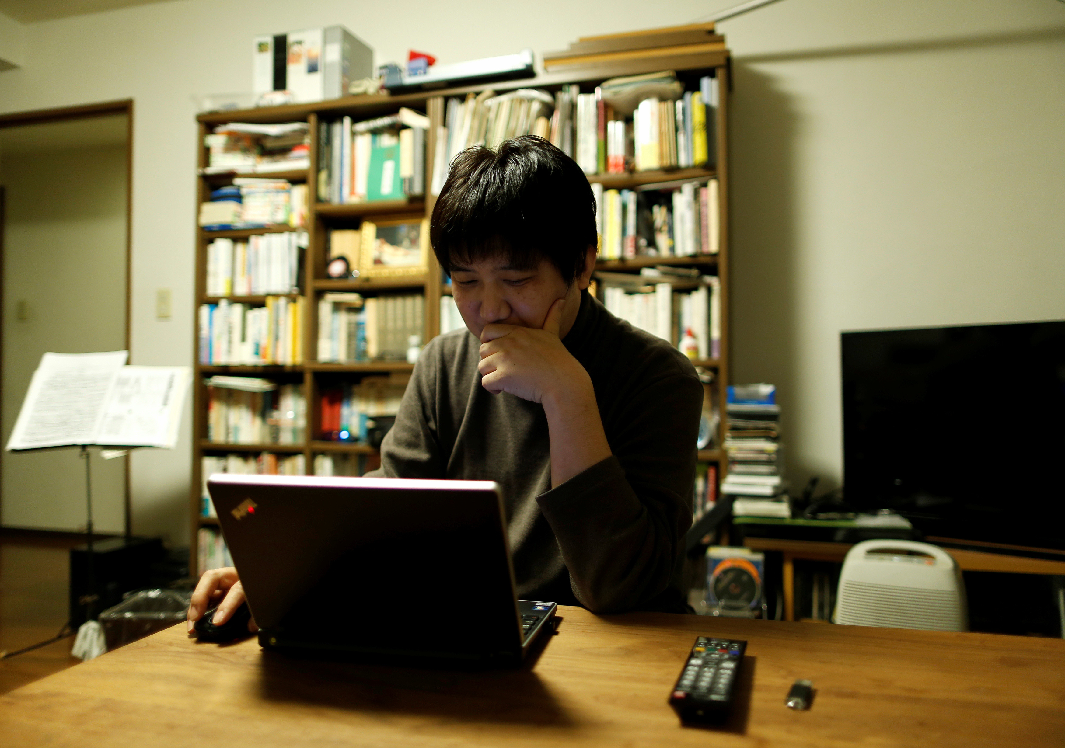Seijiro Katsura, a 44-year-old office worker, checks market rates for investment opportunities using his laptop computer at his home in Tokyo, Japan December 10, 2016. Picture taken December 10, 2016.  REUTERS/Issei Kato - RC129D1D24F0
