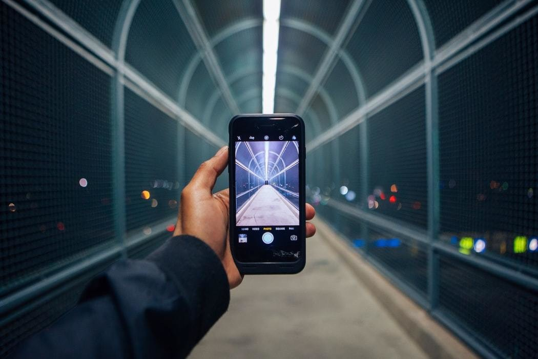A person holds a smartphone taking a photo in a tunnel.