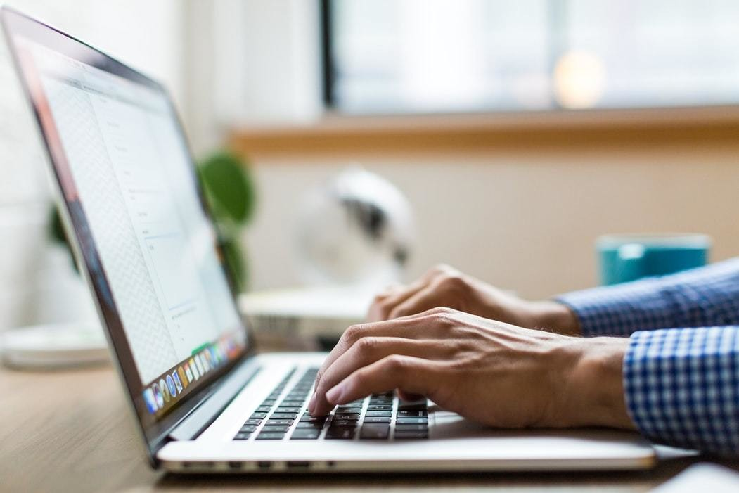 Image of a man working on a laptop