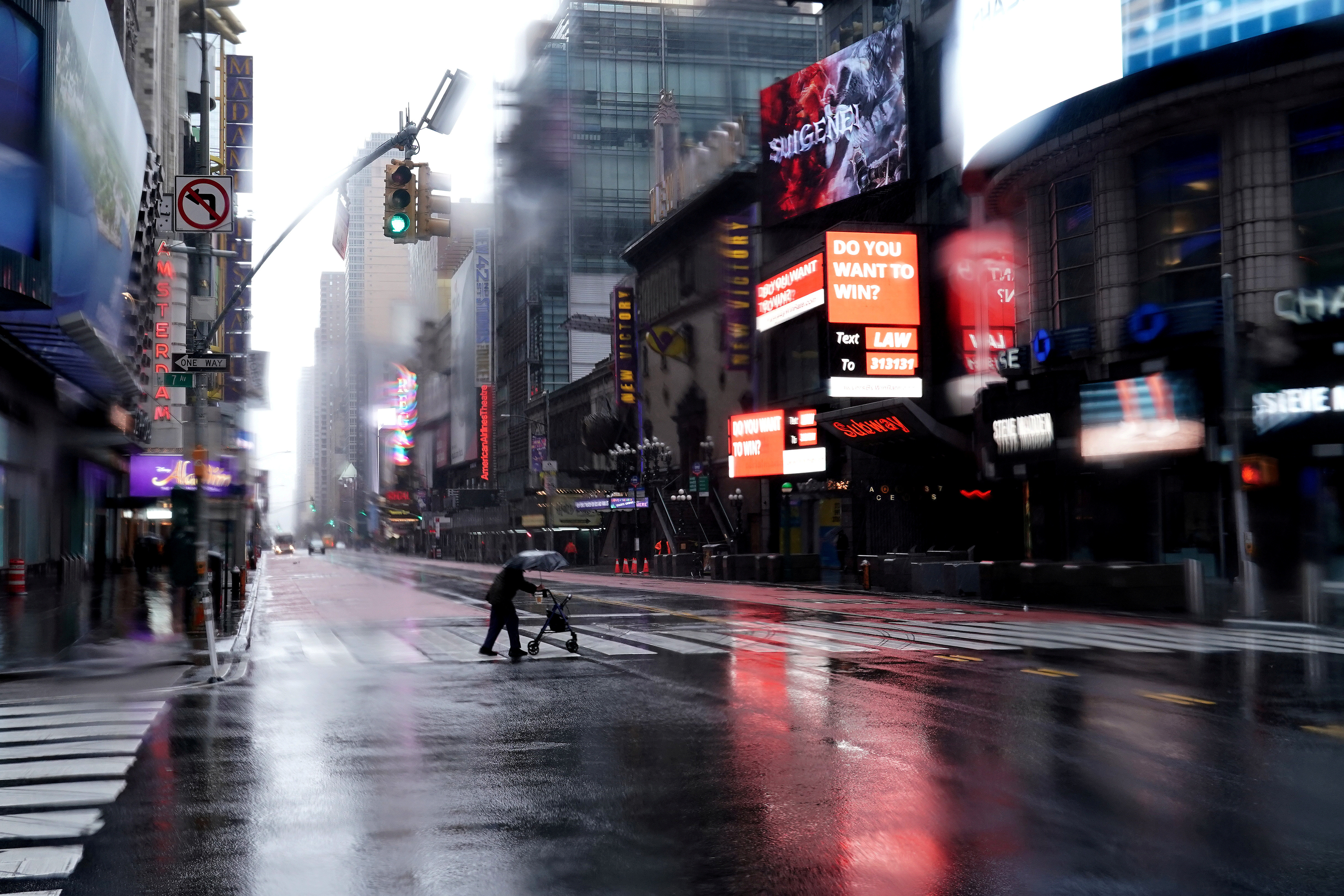 A person with a walker crosses 42nd Street in a mostly deserted Times Square following the outbreak of Coronavirus disease (COVID-19), in the Manhattan borough of New York City, New York, U.S., March 23, 2020. REUTERS/Carlo Allegri     TPX IMAGES OF THE DAY - RC2UPF9LAE4V