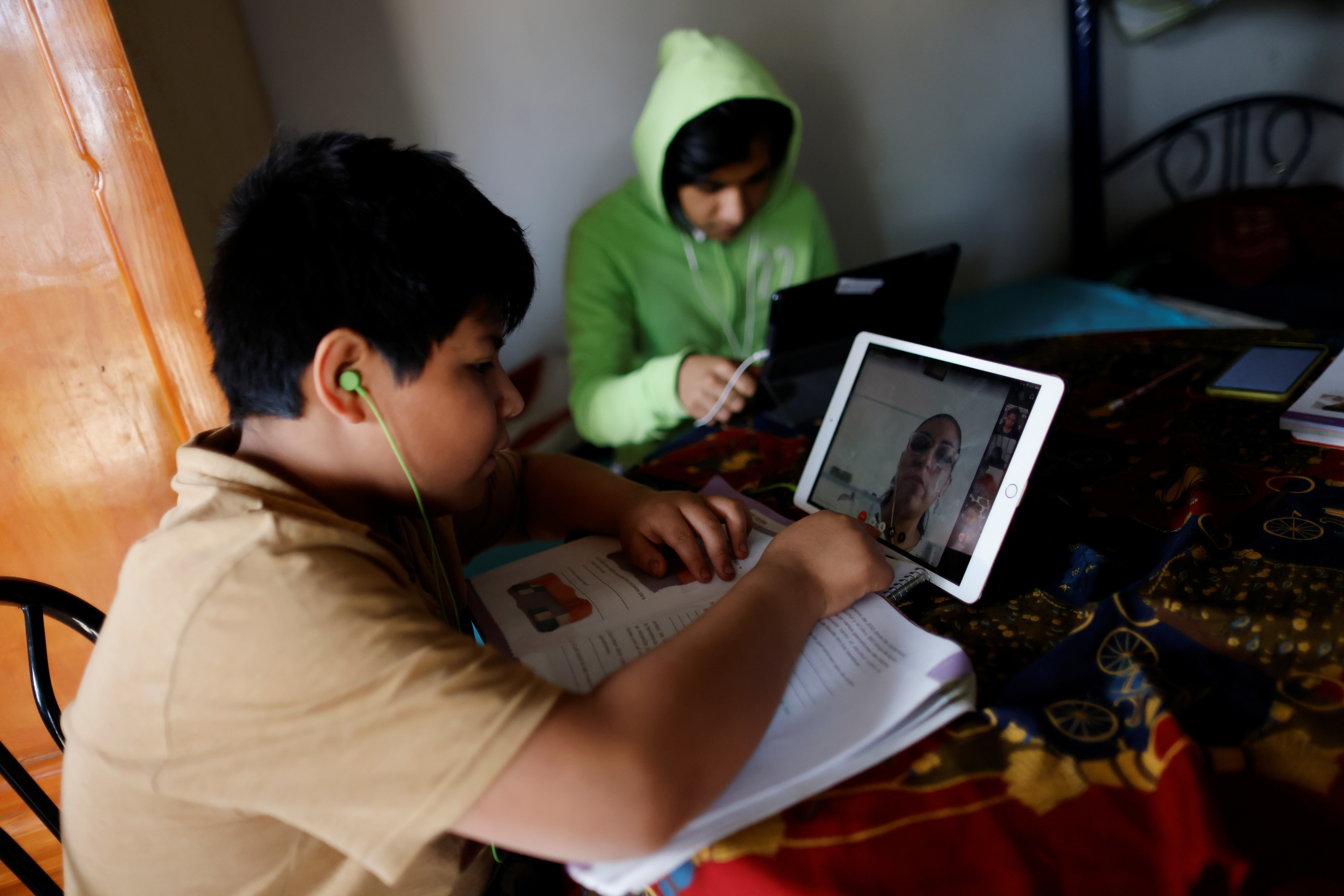 Max Gallardo, 11, listens to his teacher from a tablet during a lesson as his brother looks at his tablet, as Mexico marks one year anniversary of homeschooling after the schools closed due to the coronavirus disease (COVID-19) pandemic, in Mexico City, Mexico March 17, 2021. Picture taken March 17, 2021.REUTERS/Carlos Jasso - RC2IEM9JYSNA