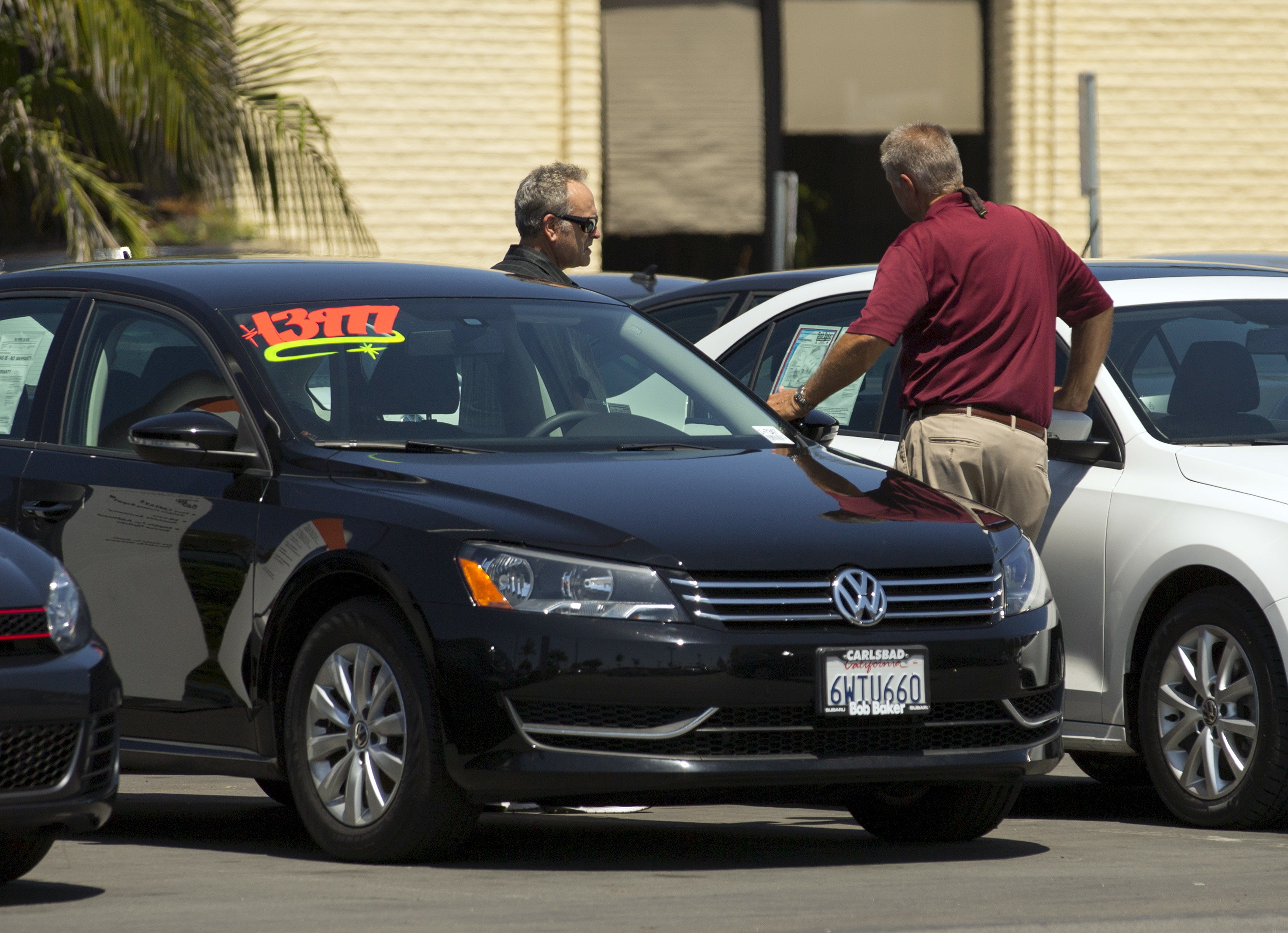 A car salesman shows a customer a vehicle on a car lot in Carlsbad, California August 28, 2015. REUTERS/Mike Blake  - GF10000185754