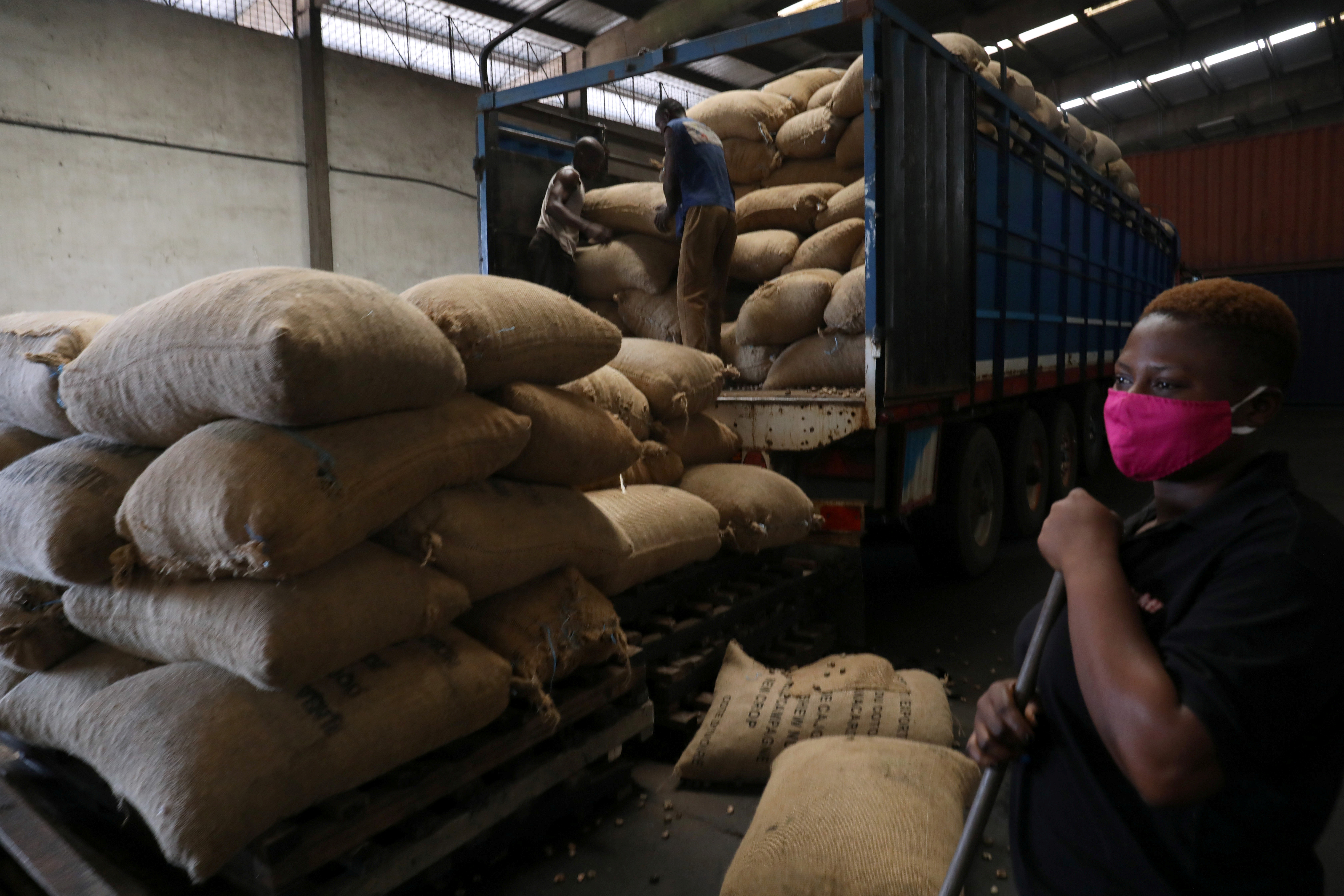 People work at a cashew nut warehouse, amid the global coronavirus disease (COVID-19) outbreak, in Abidjan, Ivory Coast May 13, 2020. Picture taken May 13, 2020. REUTERS/Luc Gnago - RC2J7H9YDQM1