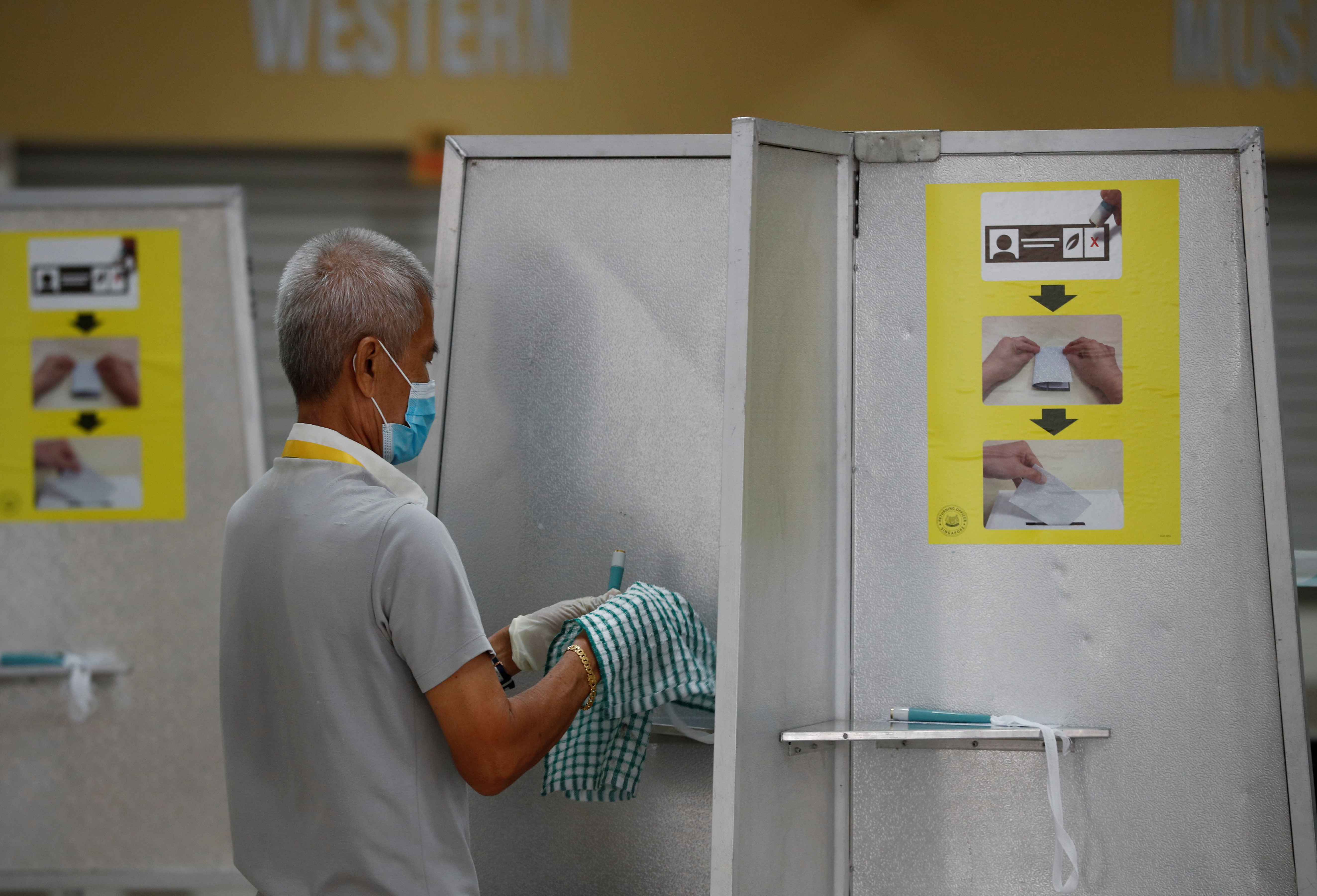 An electoral personnel sanitises self-inking pens at a ballot booth at a polling station during the general election amid the coronavirus disease (COVID-19) outbreak in Singapore July 10, 2020.  REUTERS/Edgar Su - RC22QH9MX50Z