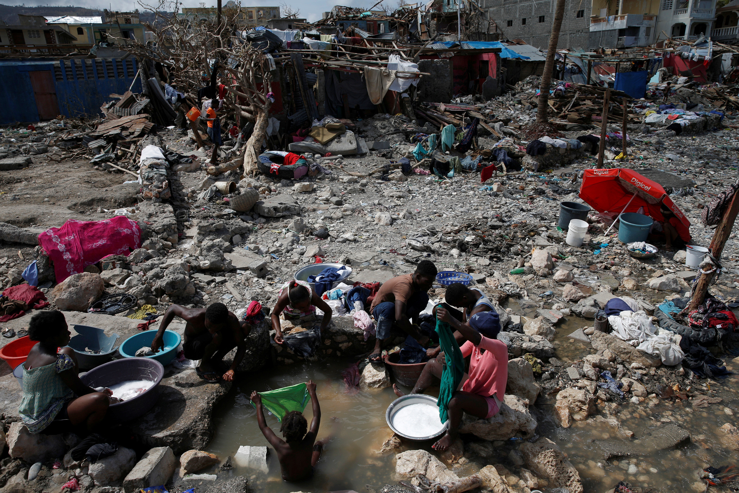 image of people washing their clothes on a beach near destroyed houses after Hurricane Matthew hit Jeremie, Haiti.