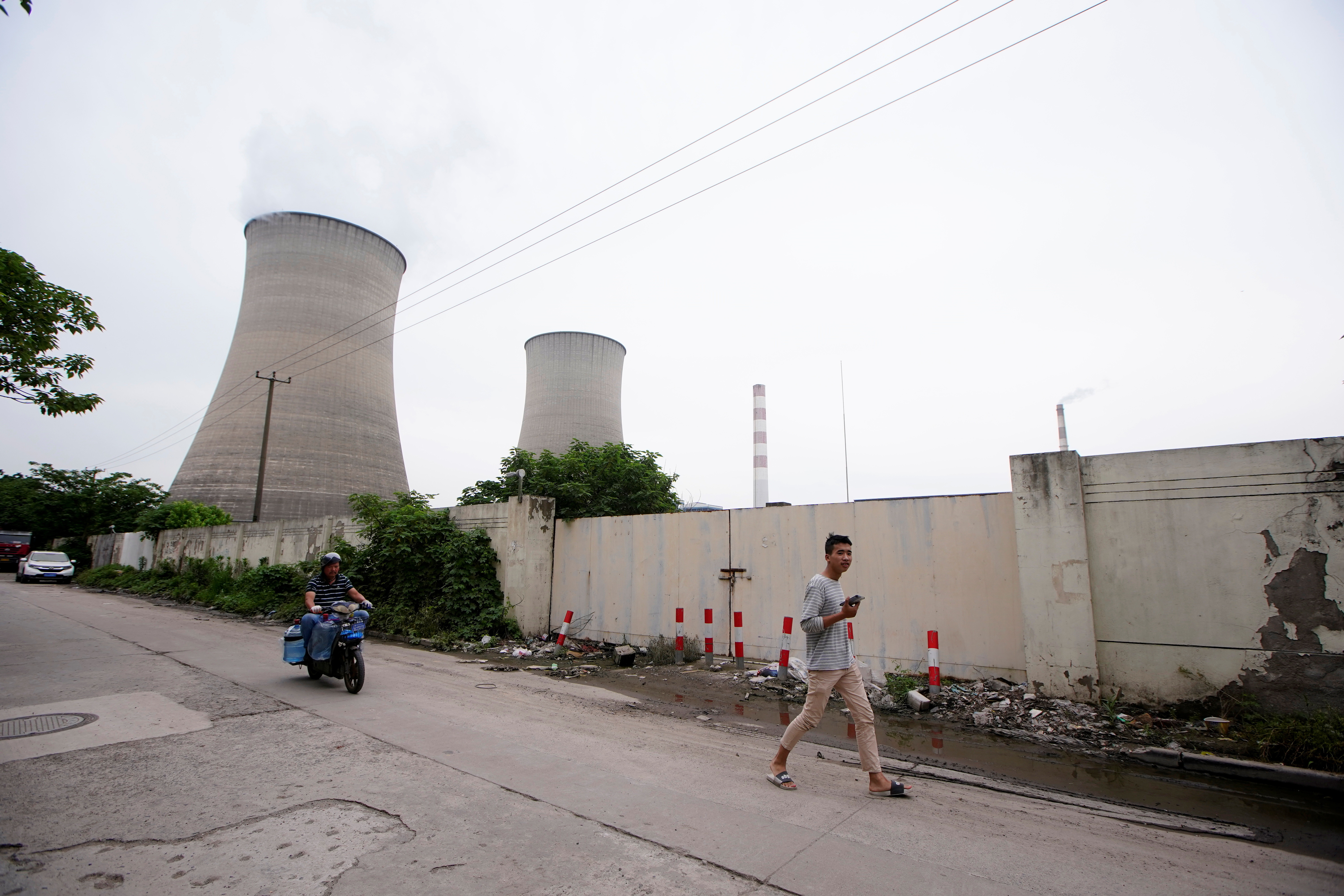 A man walks past a coal-fired power plant in Shanghai, China, May 28, 2021.