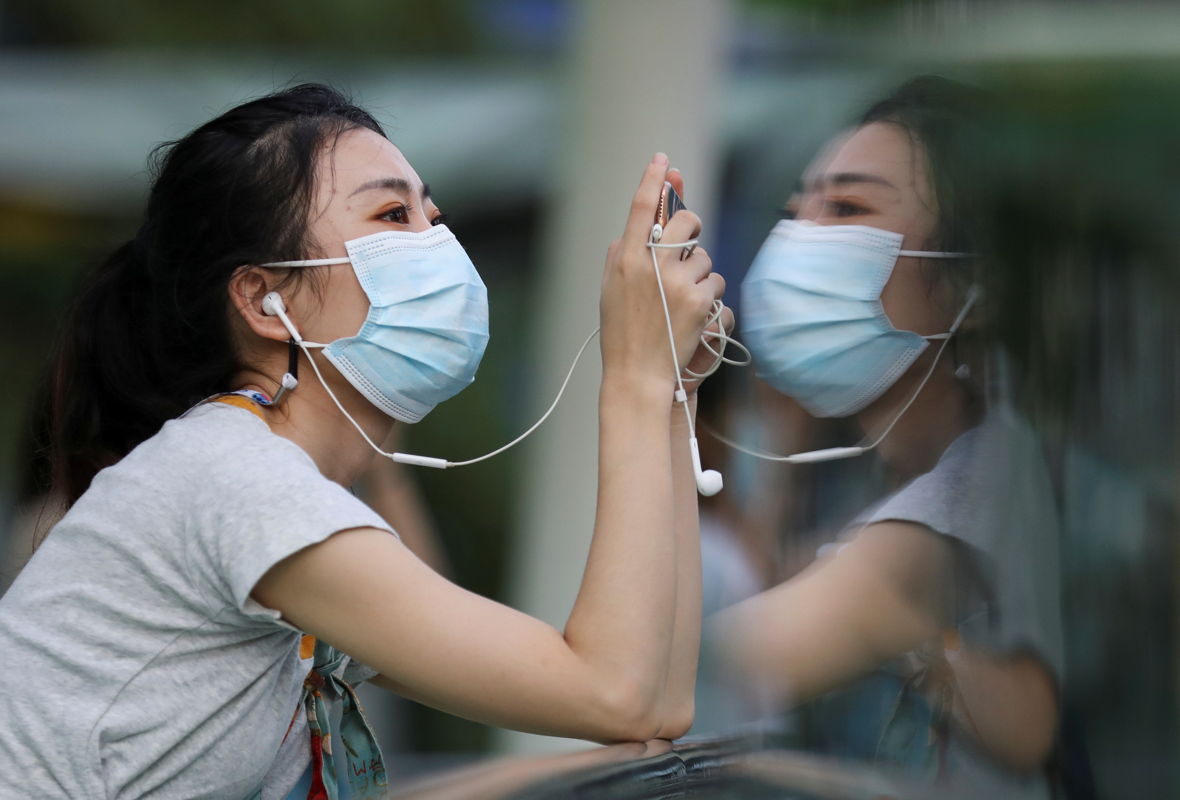 A woman wears a protective face mask as she looks at her mobile phone amid the outbreak of the coronavirus disease (COVID-19), in Bangkok, Thailand September 30, 2020. REUTERS/Soe Zeya Tun - RC219J9B1TR3