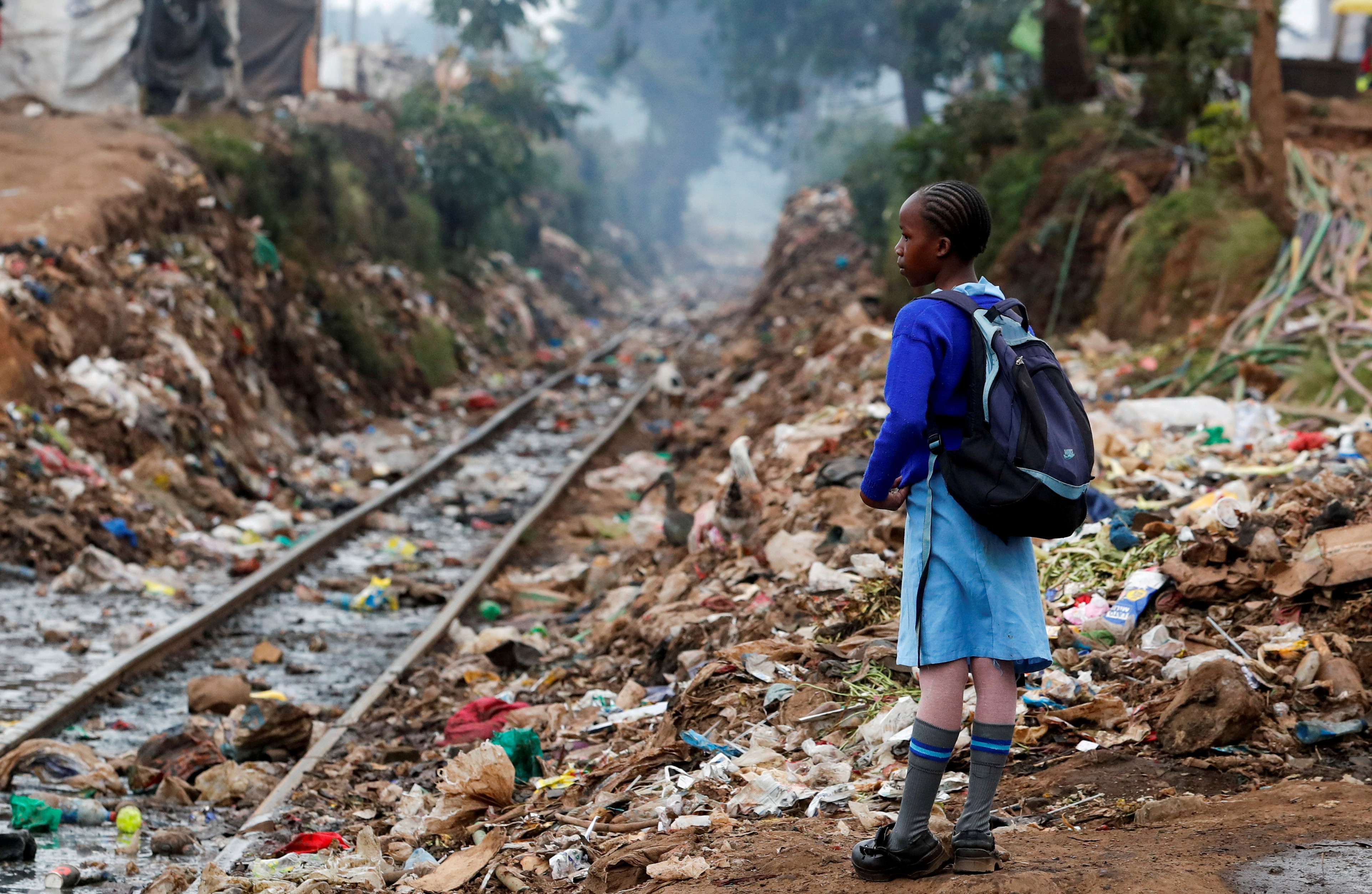 A schoolgirl stands next to the Kenya-Uganda railway line during the partial reopening of schools, after the government scrapped plans to cancel the academic year due to the coronavirus disease (COVID-19) pandemic, in Kibera slums of Nairobi, Kenya October 12, 2020. REUTERS/Thomas Mukoya     TPX IMAGES OF THE DAY - RC2WGJ9G86NR