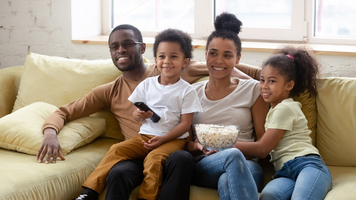 Spouses and kids spend lazy weekend together seated on couch in living room eating pop-corn choosing show or movie on TV. Happy family activity at home, free time and fun concept