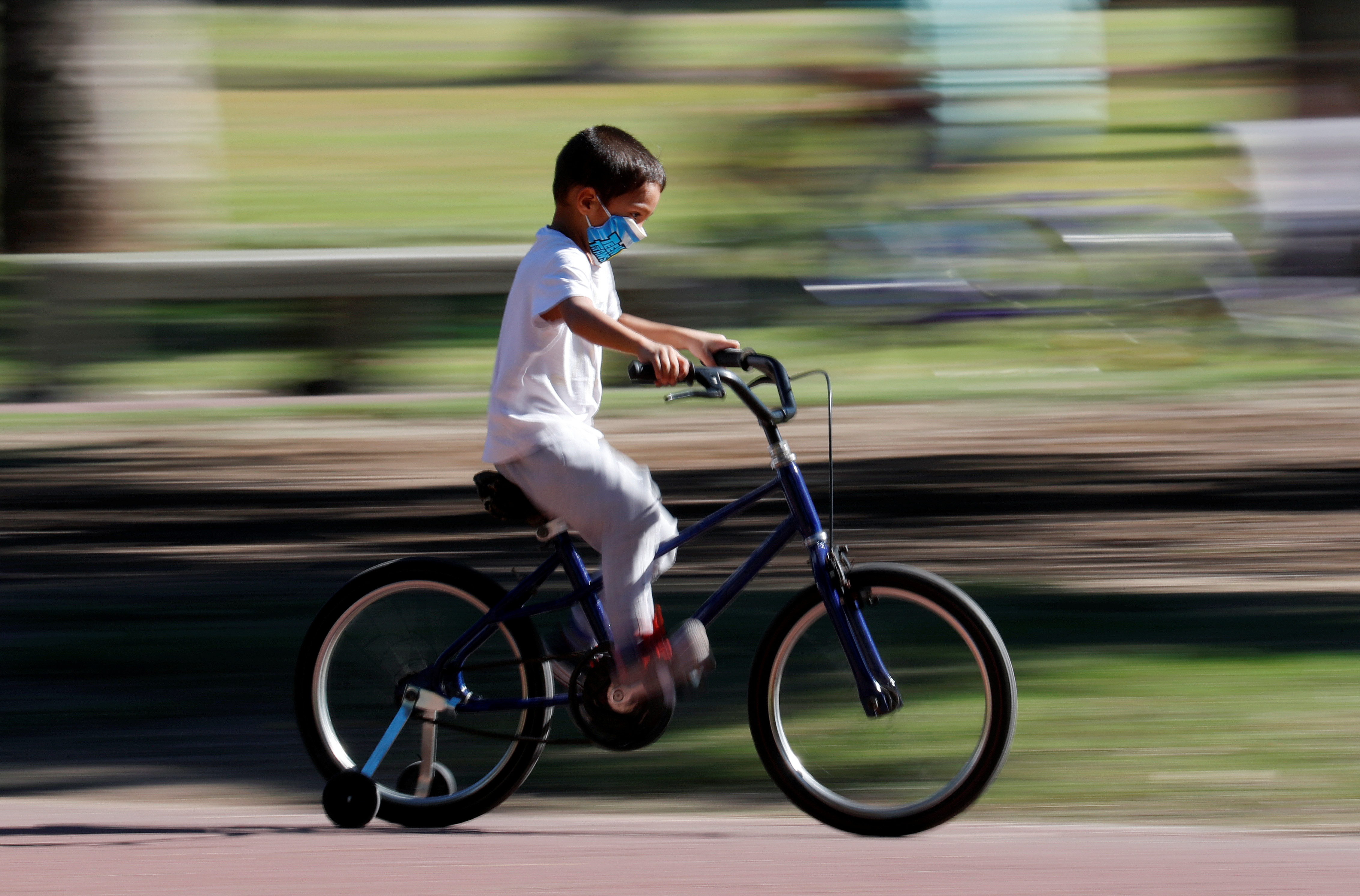 A boy wearing a face mask rides a bike in a park after restrictions were partially lifted for children in the city of Buenos Aires during the coronavirus disease (COVID-19) outbreak, Argentina May 16, 2020.