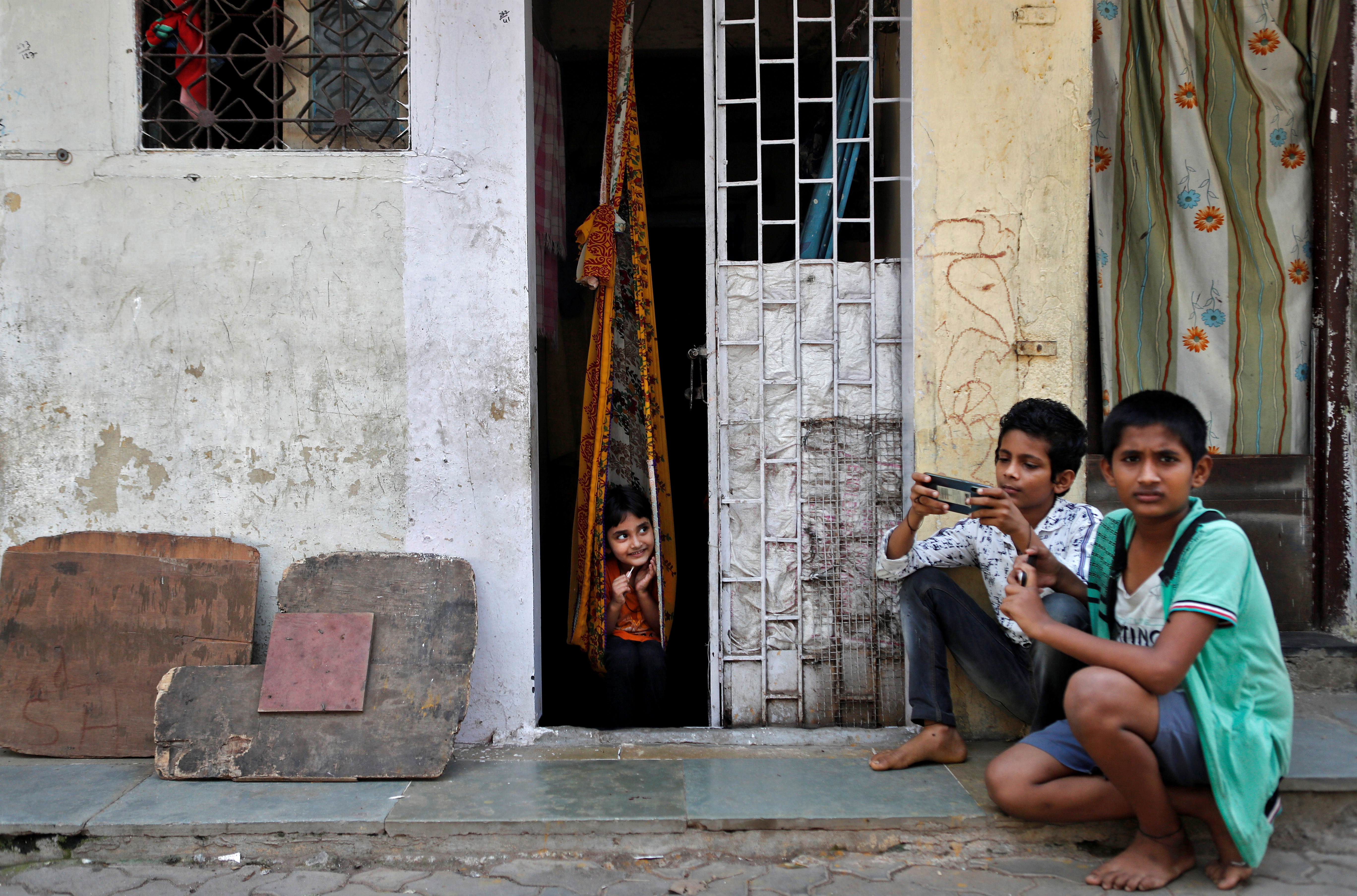 "Children play outside a house, during a nationwide lockdown in India to slow the spread of COVID-19, in Dharavi, one of Asia's largest slums, during the coronavirus disease outbreak, in Mumbai, India, April 10, 2020. REUTERS/Francis Mascarenhas     SEARCH ""CORONAVIRUS MUMBAI SLUM"" FOR THIS STORY. SEARCH ""WIDER IMAGE"" FOR ALL STORIES. - RC2Z7G9BIT8M"
