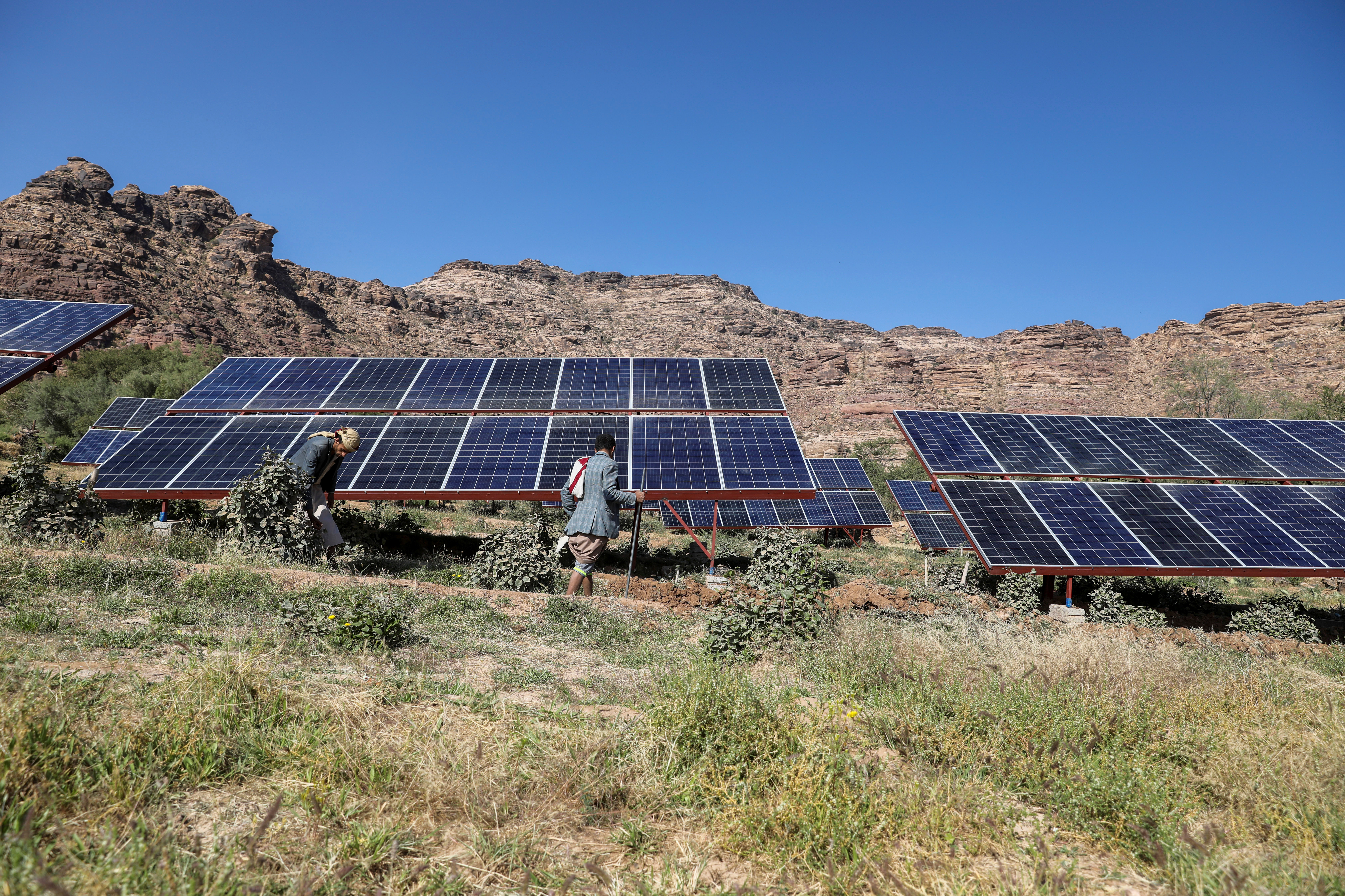 Farmers work next to solar panels at a farmland in Wadi Dhahr near Sanaa, Yemen October 28, 2019. Picture taken October 28, 2019. REUTERS/Khaled Abdullah - RC21DD9BIQVV