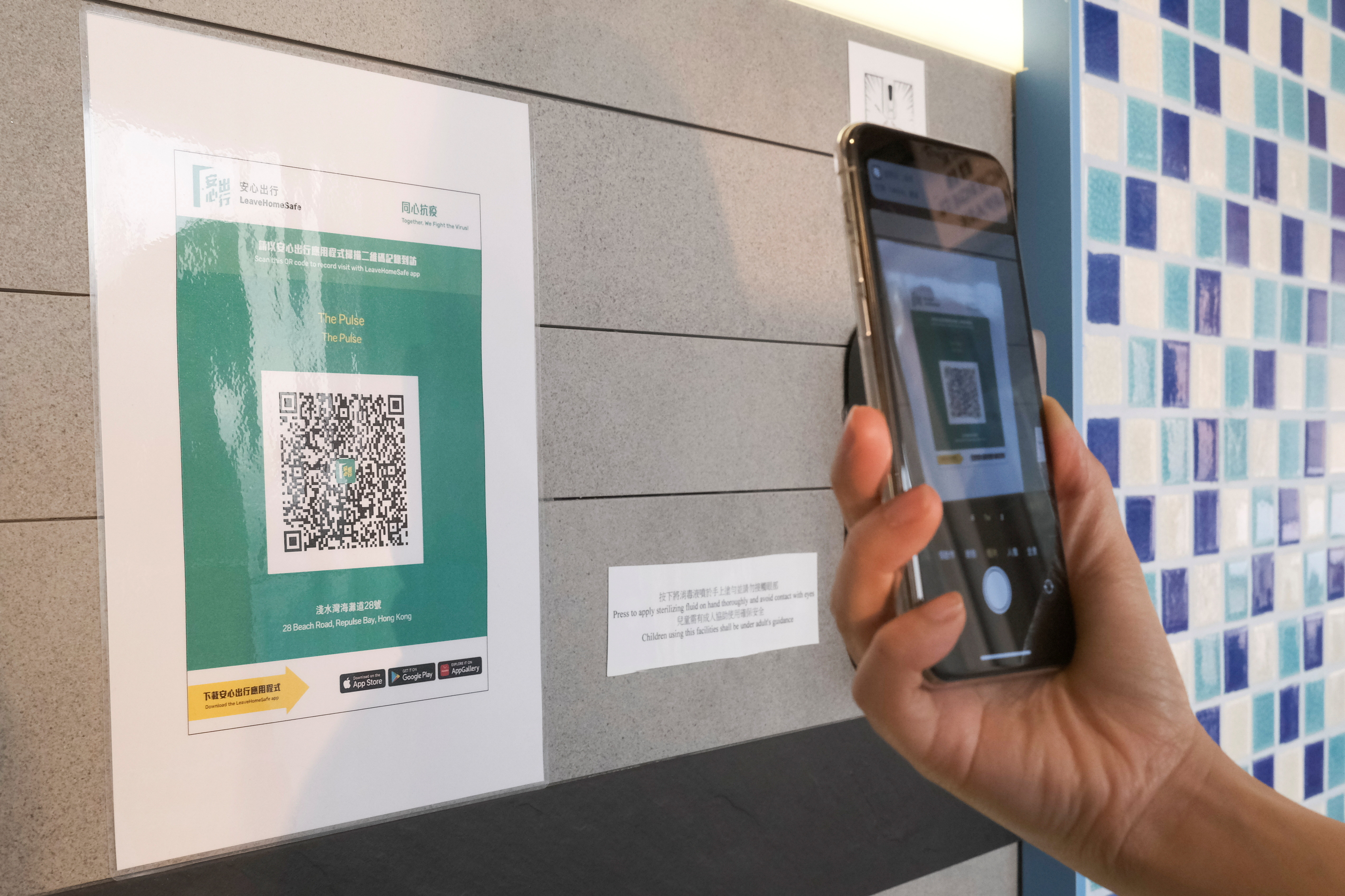 """A QR code for the """"LeaveHomeSafe"""" COVID-19 contact-tracing app is posted at a shopping mall, following the coronavirus disease (COVID-19) outbreak, in Hong Kong, China February 16, 2021. REUTERS/Tyrone Siu - RC2NTL9XCG3V"""