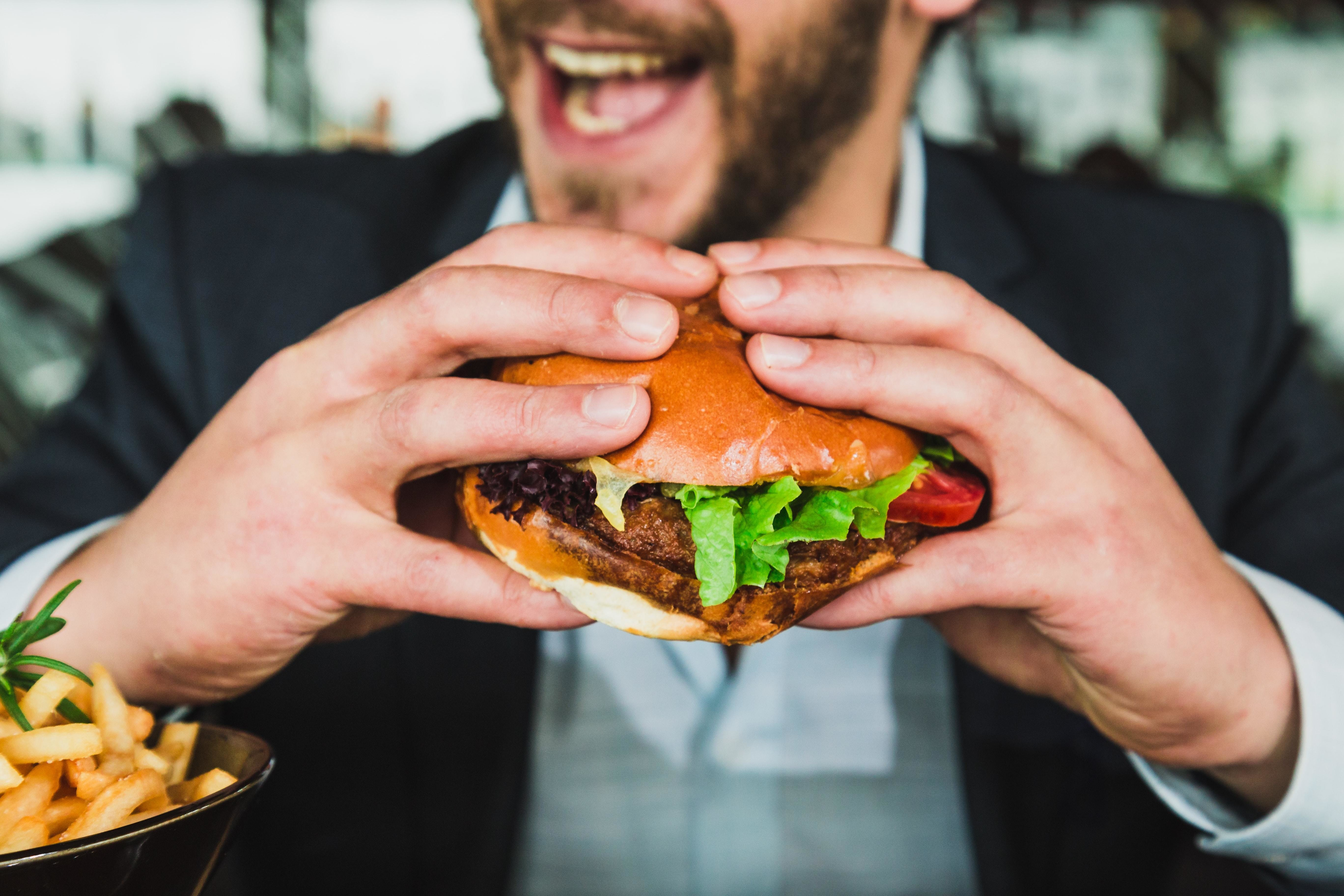 A picture of a man hold a big yummy burger about to bite into it, as a study reveals how we make food choices.