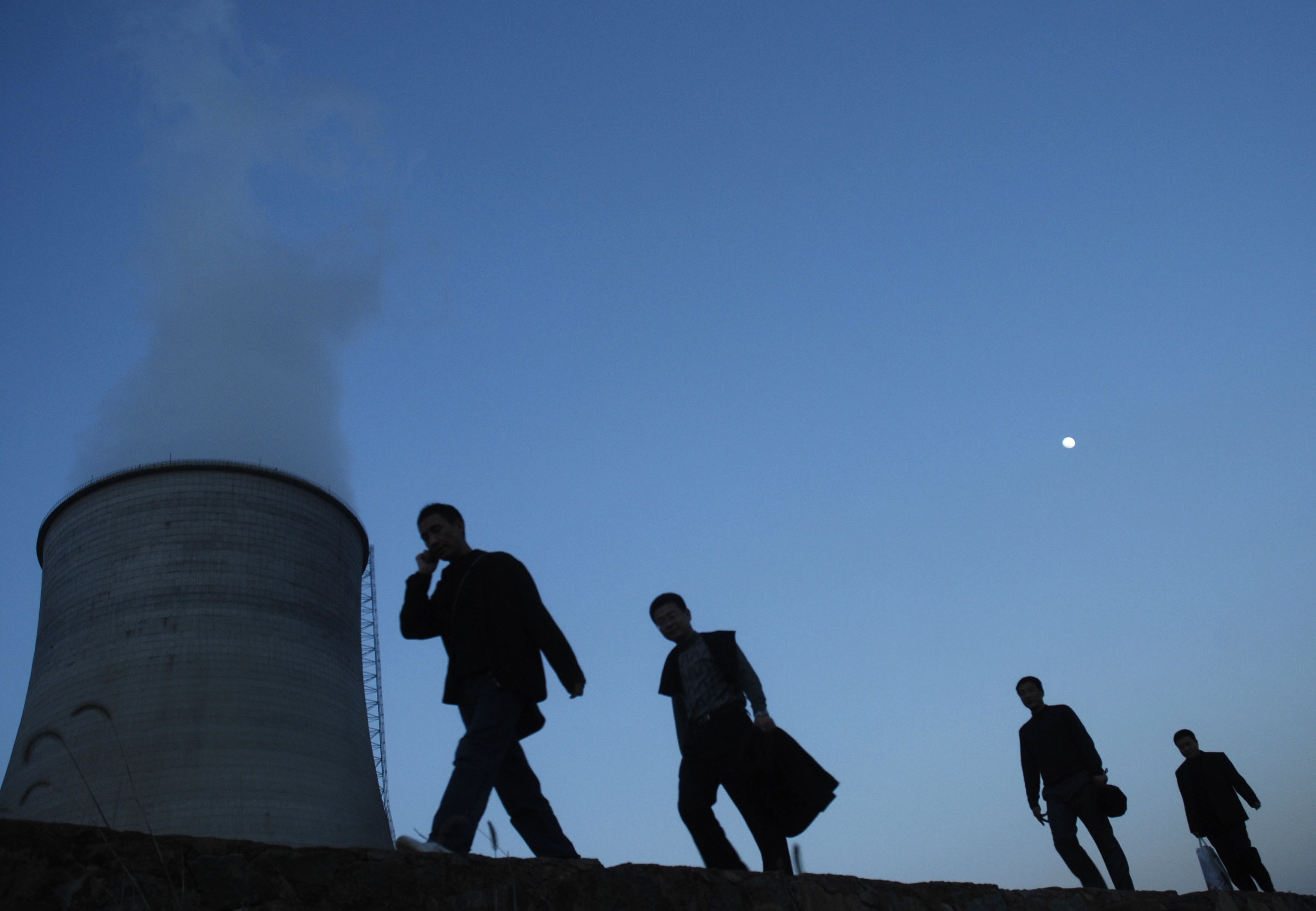 People walk on a street past a power plant's cooling tower in Yingtan, Jiangxi province December 11, 2008. Picture taken December 11, 2008. REUTERS/Stringer (CHINA).  CHINA OUT. NO COMMERCIAL OR EDITORIAL SALES IN CHINA. - GM1E4CC14A801